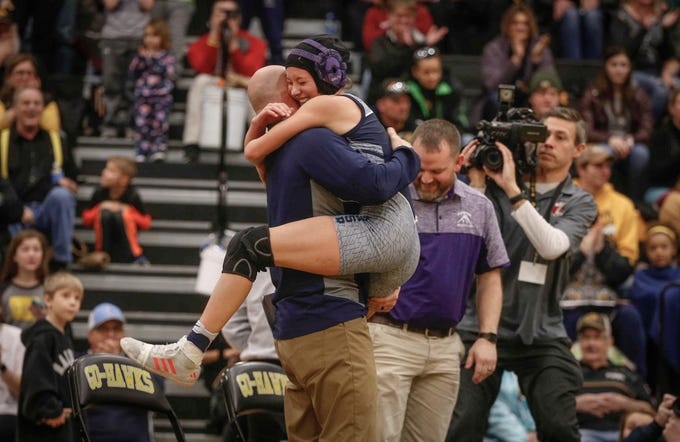 AGWSR junior Ali Gerbracht hugs her coach after making state history on Saturday, Jan. 19, 2019, during the first Iowa girls state wrestling tournament at Waverly-Shell Rock High School in Waverly. After a win at 106-pounds, Gerbracht was the first Iowa high school girl to win on state title on Saturday.