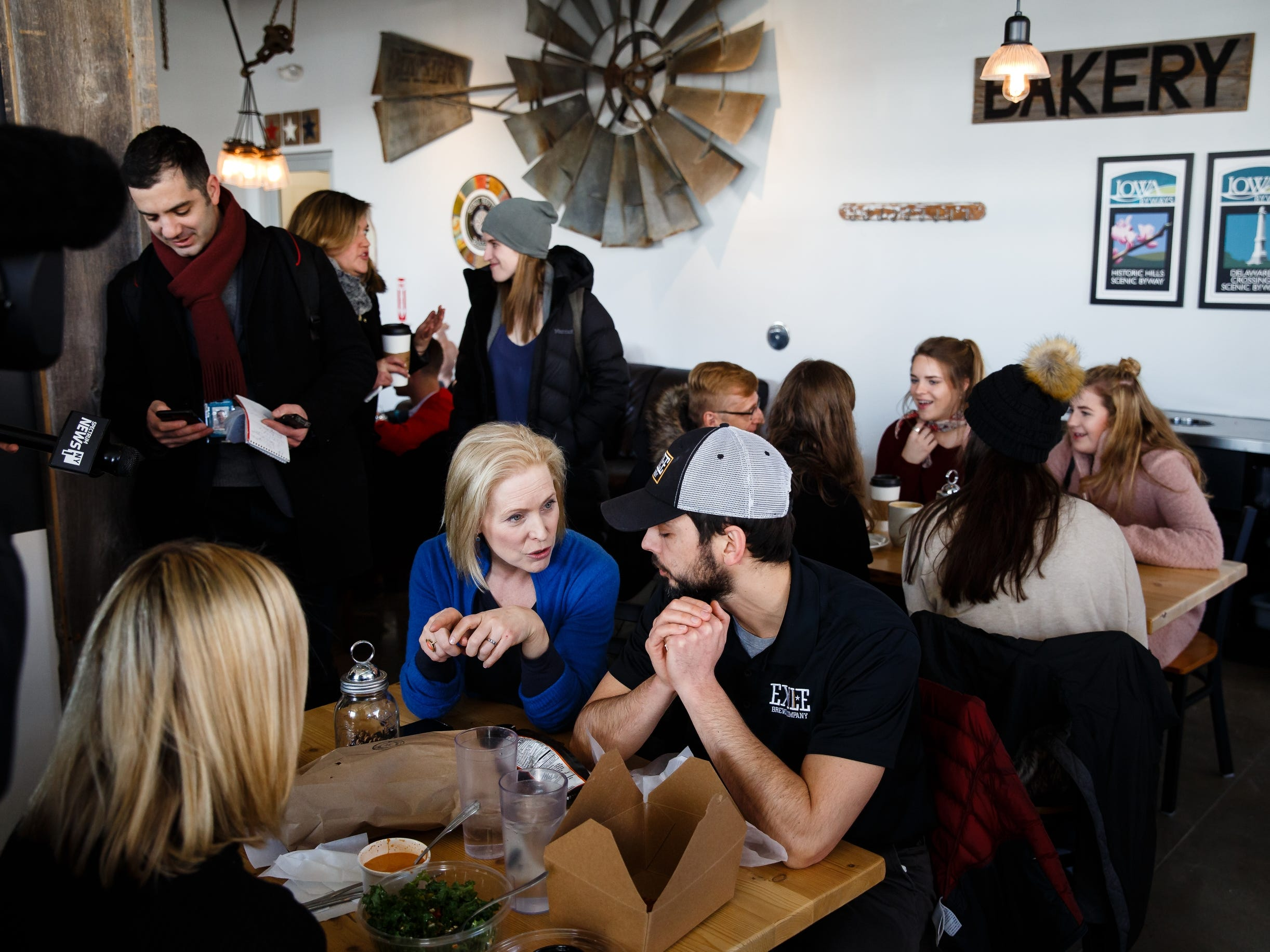 During a walking tour of the East Village, Sen. Kirsten Gillibrand of New York stops at Scenic Route bakery to talk to voters including R.J. Tursi, center, on Saturday, Jan. 19, 2019, in Des Moines.