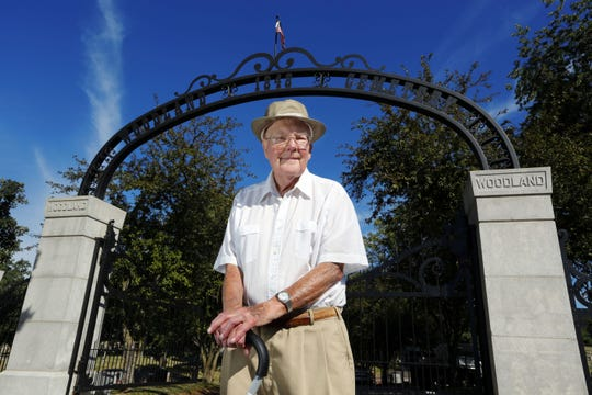 Gerald LaBlanc stands in front of the memorial arch at the entrance to Woodland Cemetery in 2013. He led a $70,000 fundraising effort to erect the arch.