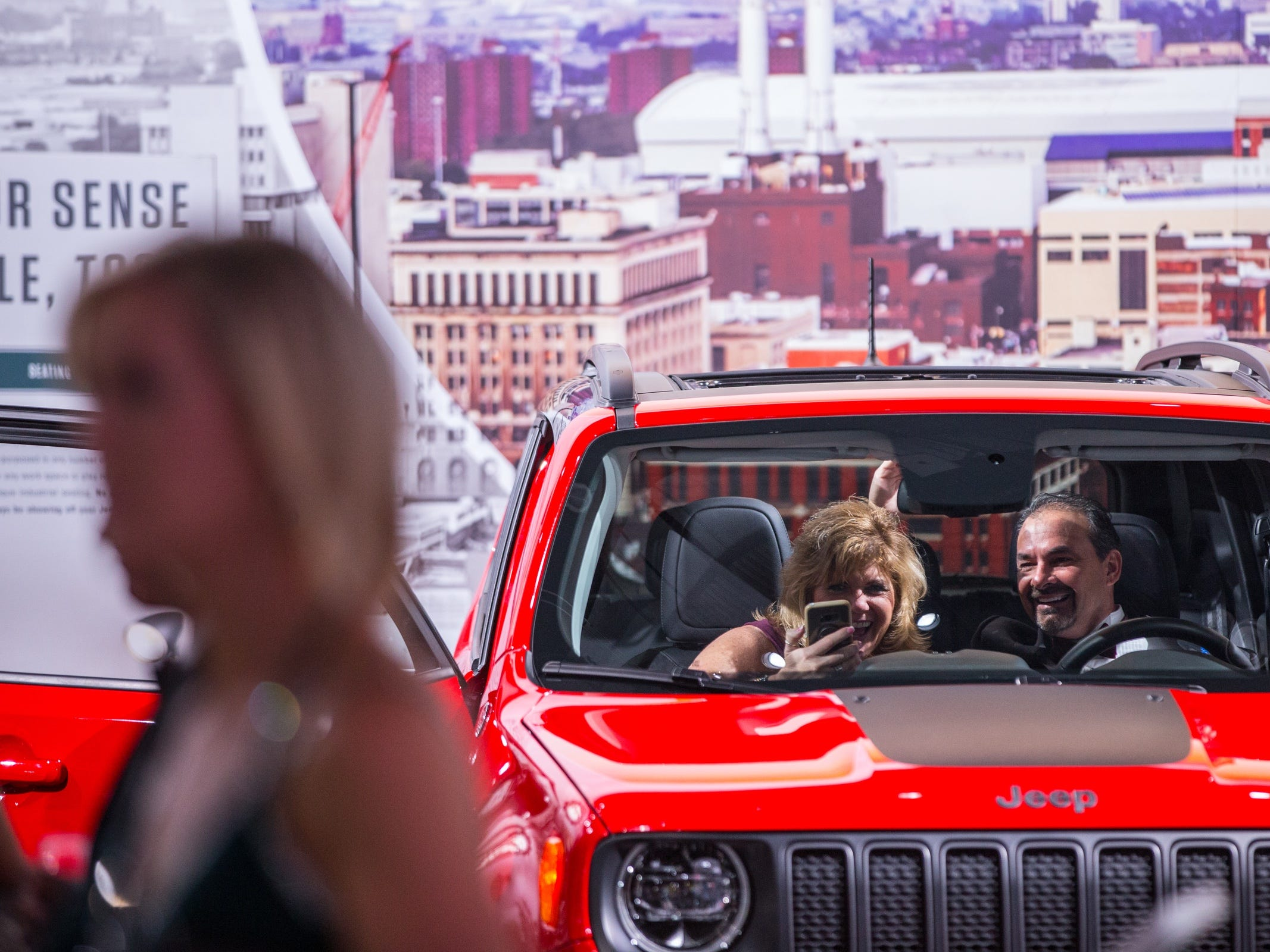 Dan Spagnoletti of Howell and his wife Sheryl Spagnoletti take a photo in a Jeep Renegade while looking at car for their child during the 2019 North American International Auto Show Charity Preview at Cobo Center in Detroit on Friday, January 18, 2019.