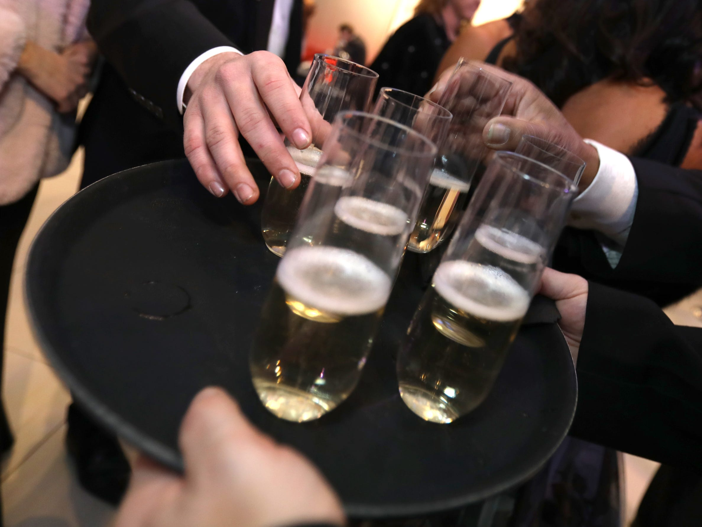 Champagne being served before the ribbon cutting ceremony at the 2019 North American International Auto Show Charity Preview at Cobo Center in Detroit on Friday, January 18, 2019.