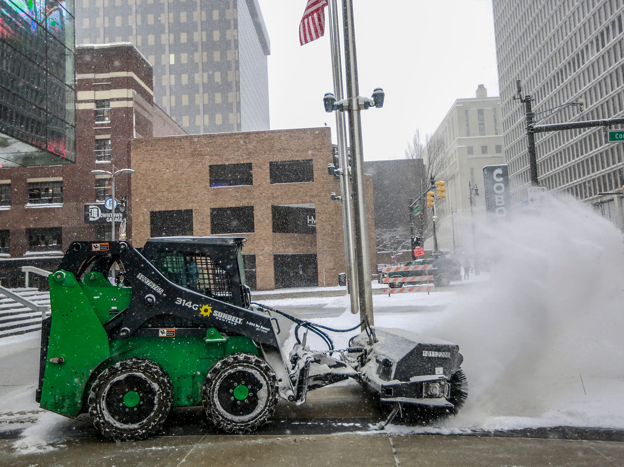 The snow is plowed from the sidewalks during the start of the public days at the North American International Auto Show at Cobo Center in downtown Detroit on Saturday, Jan. 19, 2019.