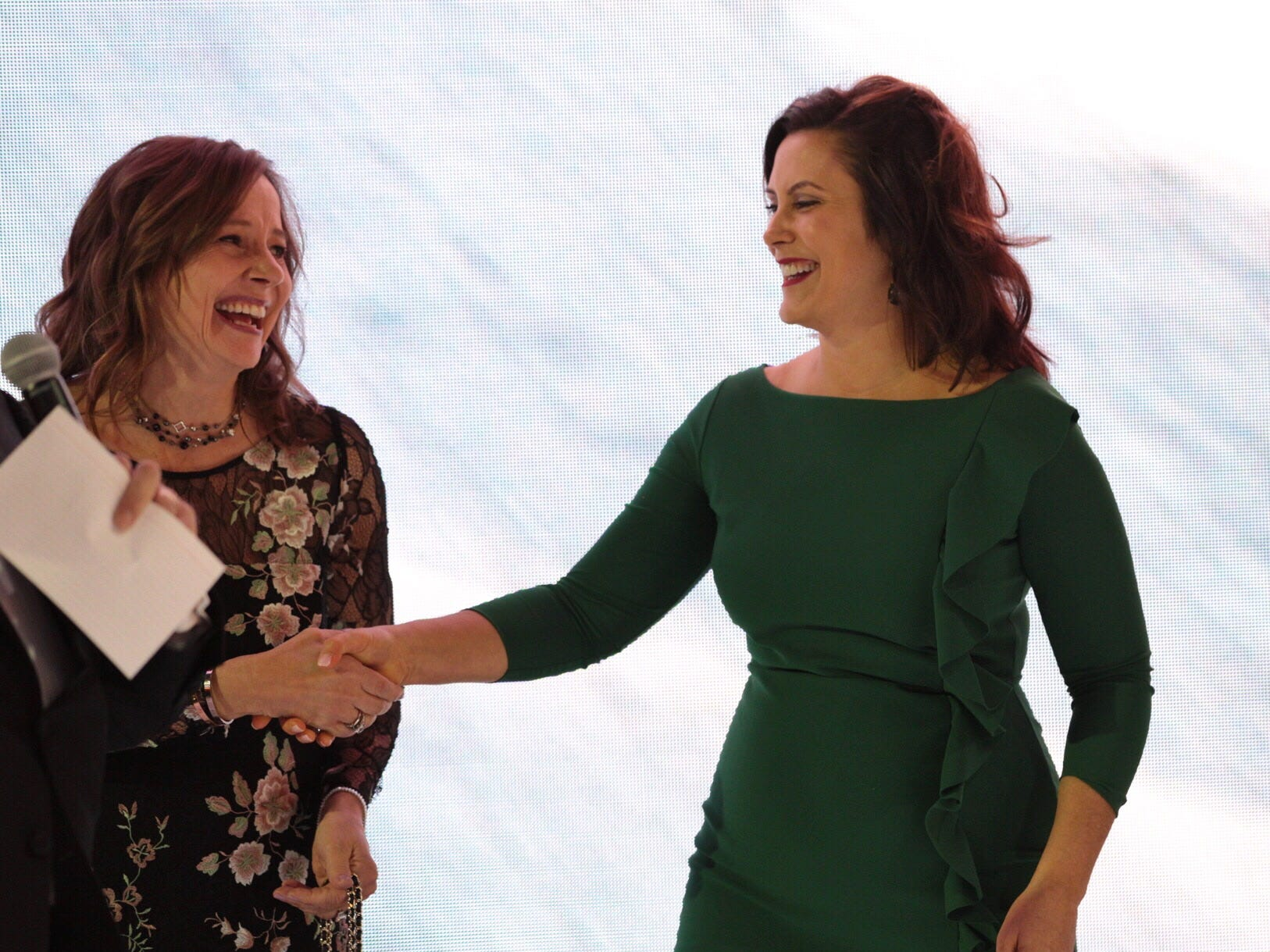 Governor Gretchen Whitmer and General Motors CEO Mary Barra shake hands while talking on the radio during the 2019 North American International Auto Show Charity Preview at Cobo Center in Detroit on Friday, January 18, 2019.