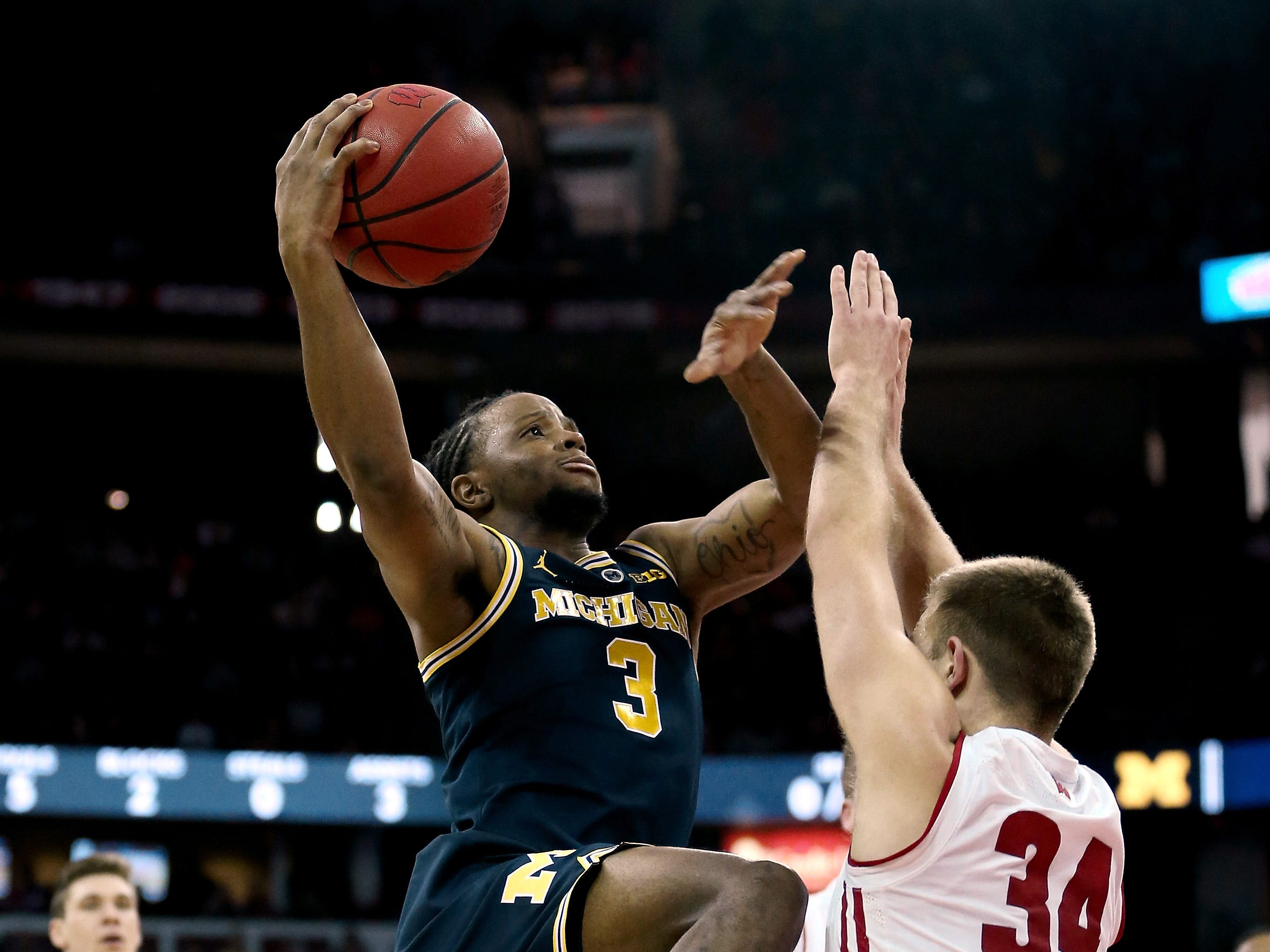 Michigan's Zavier Simpson attempts a shot while guarded by Wisconsin's Brad Davison in the first half at the Kohl Center, Jan. 19, 2019 in Madison, Wisc.