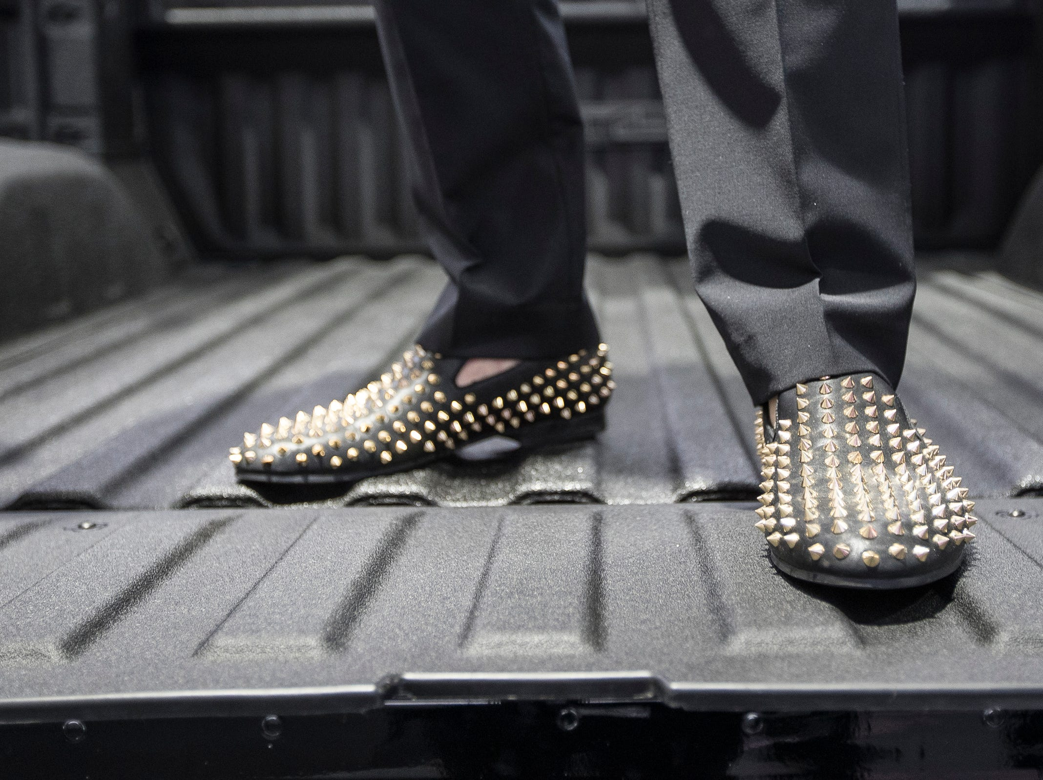 Avi Knopf of Huntington Woods shows off his shoes while standing on the bed of a 2019 GMC Sierra during the 2019 North American International Auto Show Charity Preview at Cobo Center in Detroit on Friday, January 18, 2019.