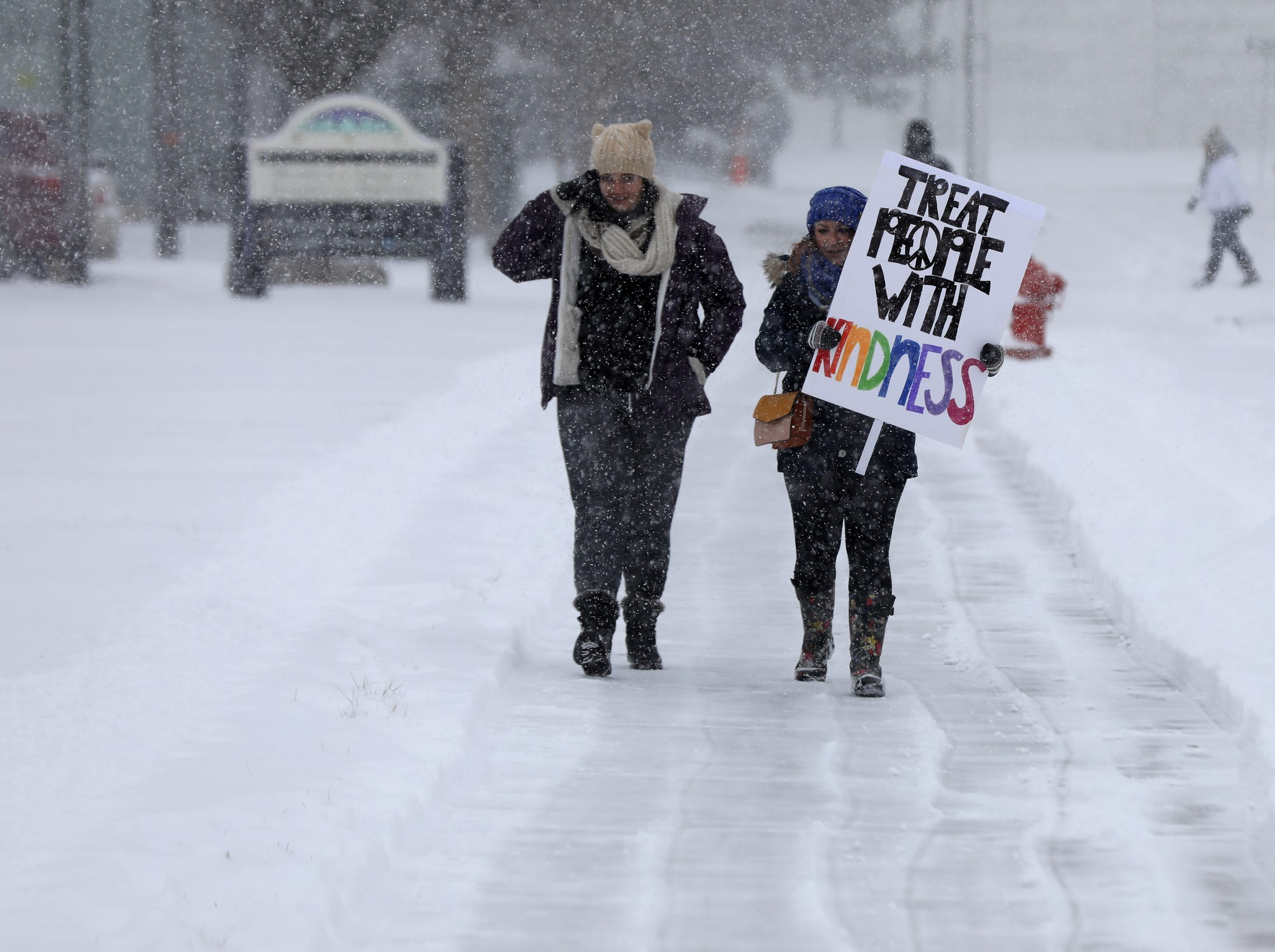 Michele Greer, 28 of Madison Heights and friend Kristy Hartman, 30 of Shelby Township battle the cold and blowing snow as they walk to the Charles H. Wright Museum of African American History for the Women's March.