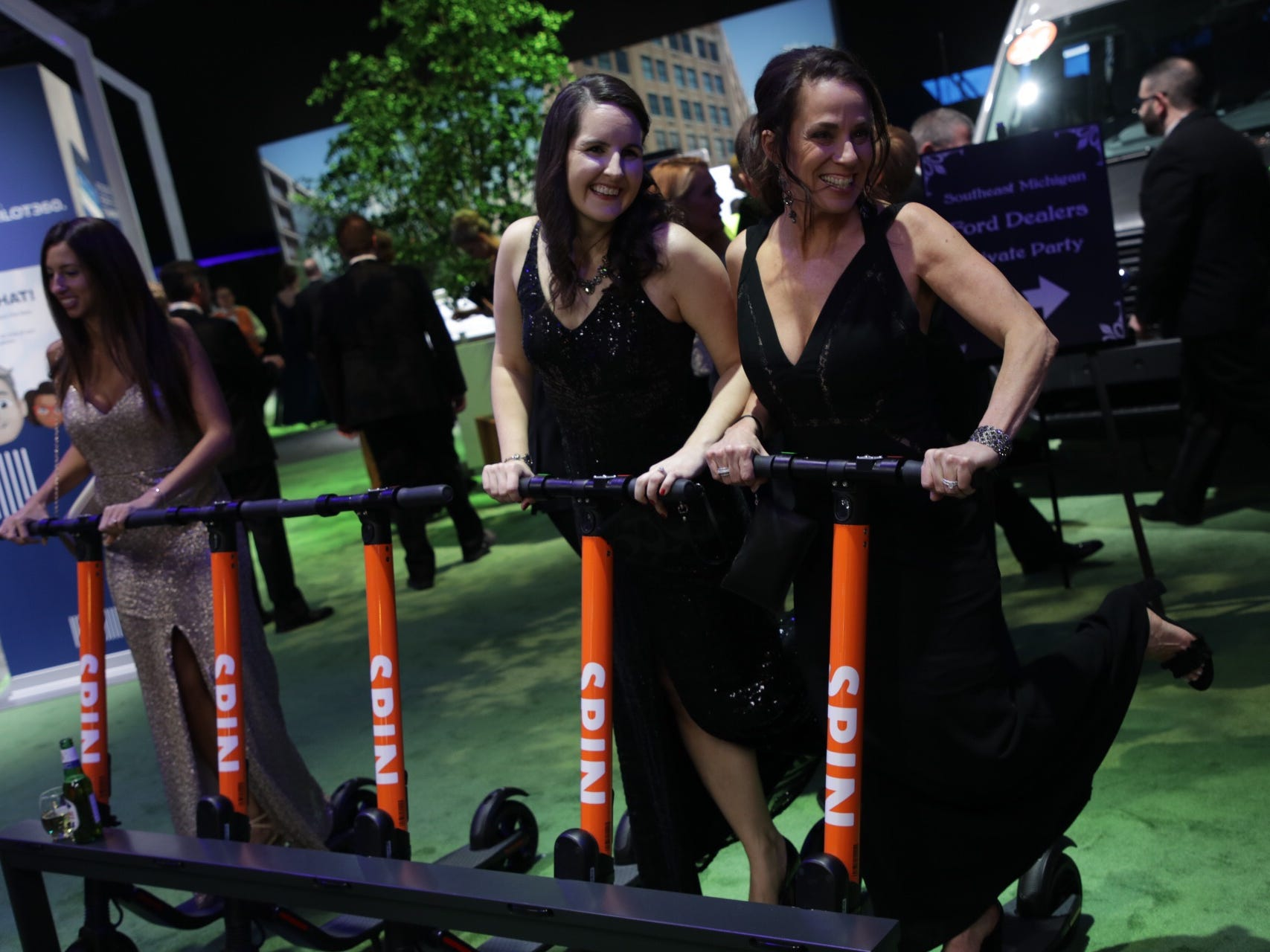Sarah Eudier, left and Lari Schroll both of West Bloomfield try Spin Scooters during the 2019 North American International Auto Show Charity Preview at Cobo Center in Detroit on Friday, January 18, 2019.