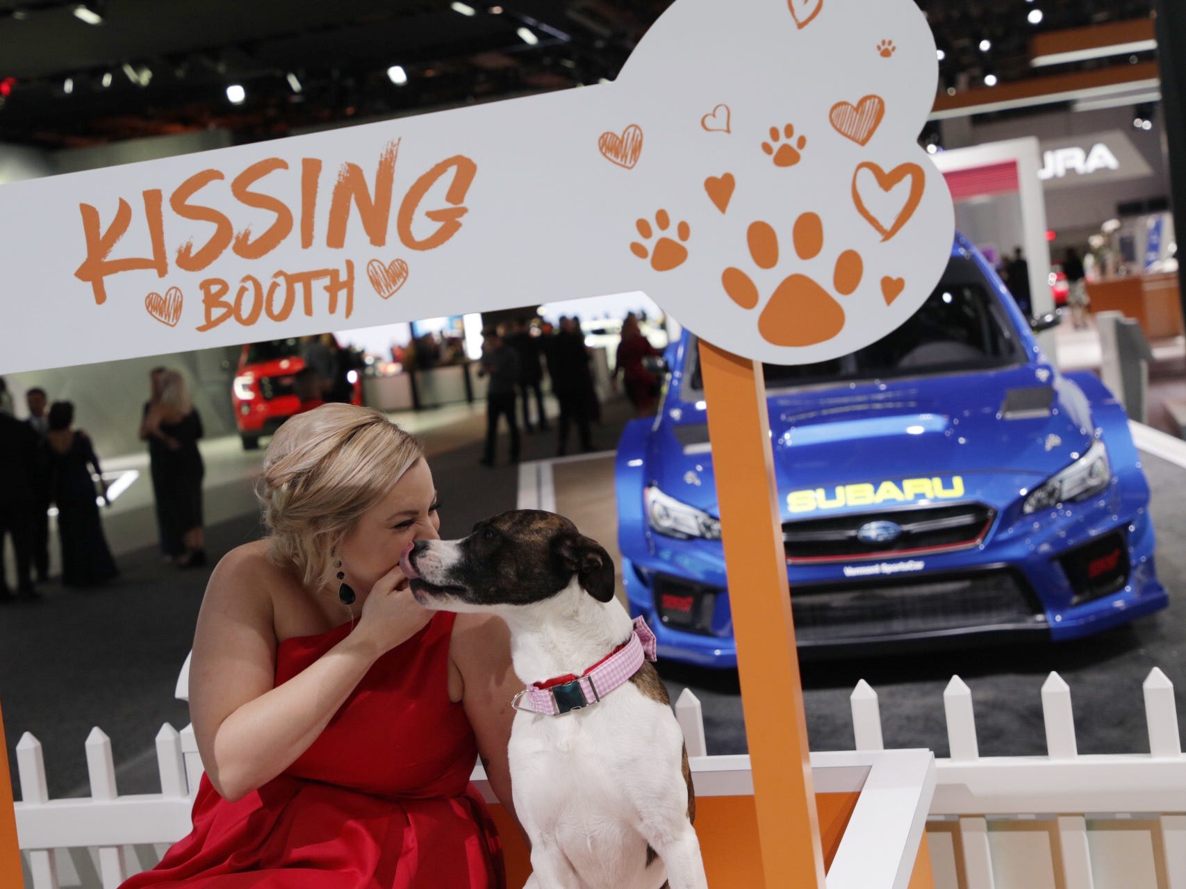 Kristin Shaw of Detroit, kisses Lama the dog during the 2019 North American International Auto Show Charity Preview at Cobo Center in Detroit on Friday, January 18, 2019.