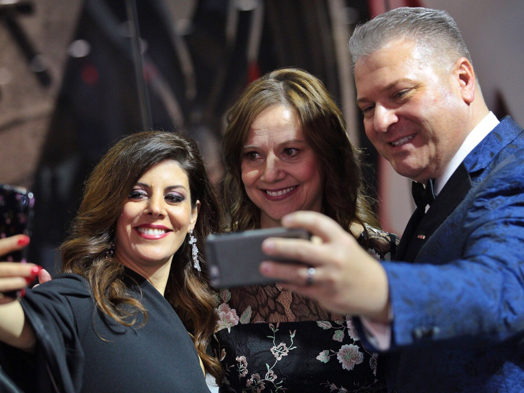 Rocky Raczkowski and wife Amalia Raczkowski take selfies with General Motors CEO Mary Barra during the 2019 North American International Auto Show Charity Preview at Cobo Center in Detroit on Friday, January 18, 2019.