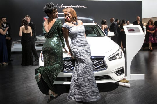Keisha Walker of West Bloomfield, left, and Barbara Locke of Detroit pose for a photo on a 2019 Infiniti Q50 during the 2019 North American International Auto Show Charity Preview at Cobo Center in Detroit on Friday, January 18, 2019.