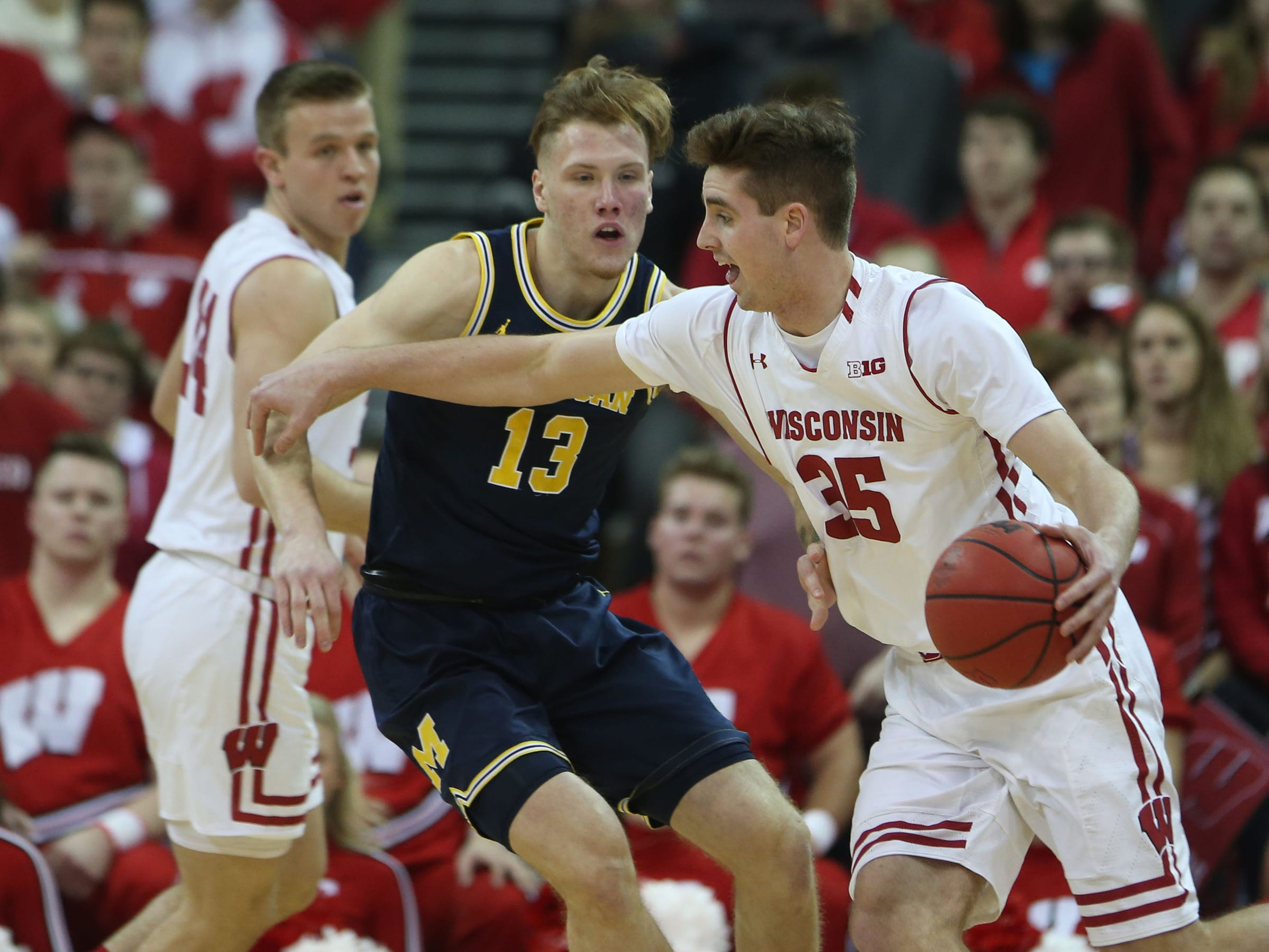 Wisconsin Badgers forward Nate Reuvers works the ball against Michigan Wolverines forward Ignas Brazdeikis at the Kohl Center, Jan. 19, 2019.