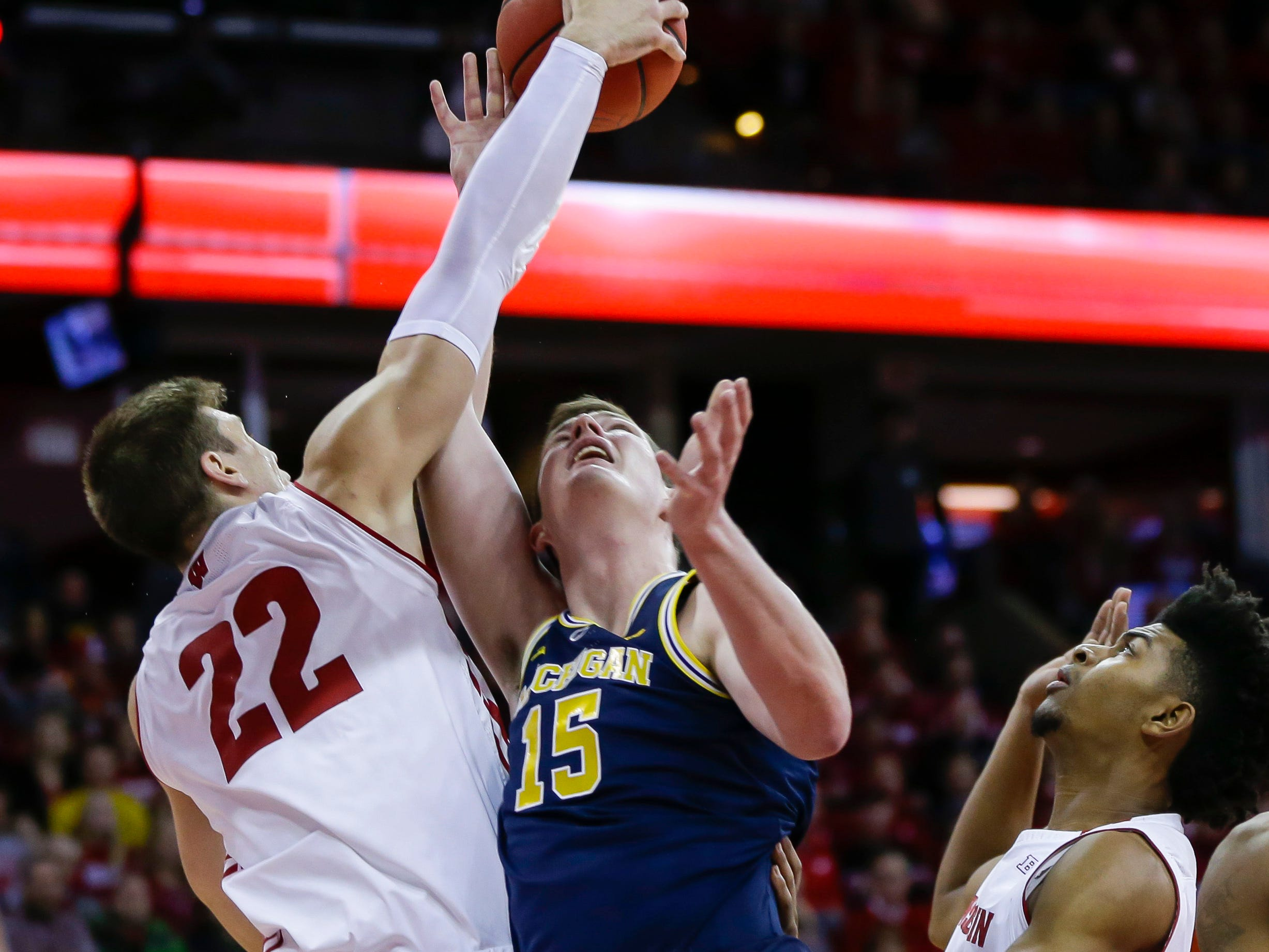 Wisconsin's Ethan Happ and Michigan's Jon Teske battle for a rebound during the first half Saturday, Jan. 19, 2019, in Madison, Wis.