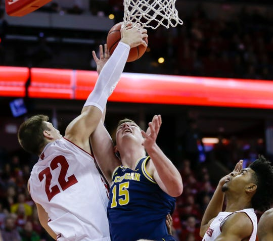 Battle of Ethan Happ and Michigan Jon Teske battle back during the first half of Saturday, January 19, 2019, in Madison, Wis.