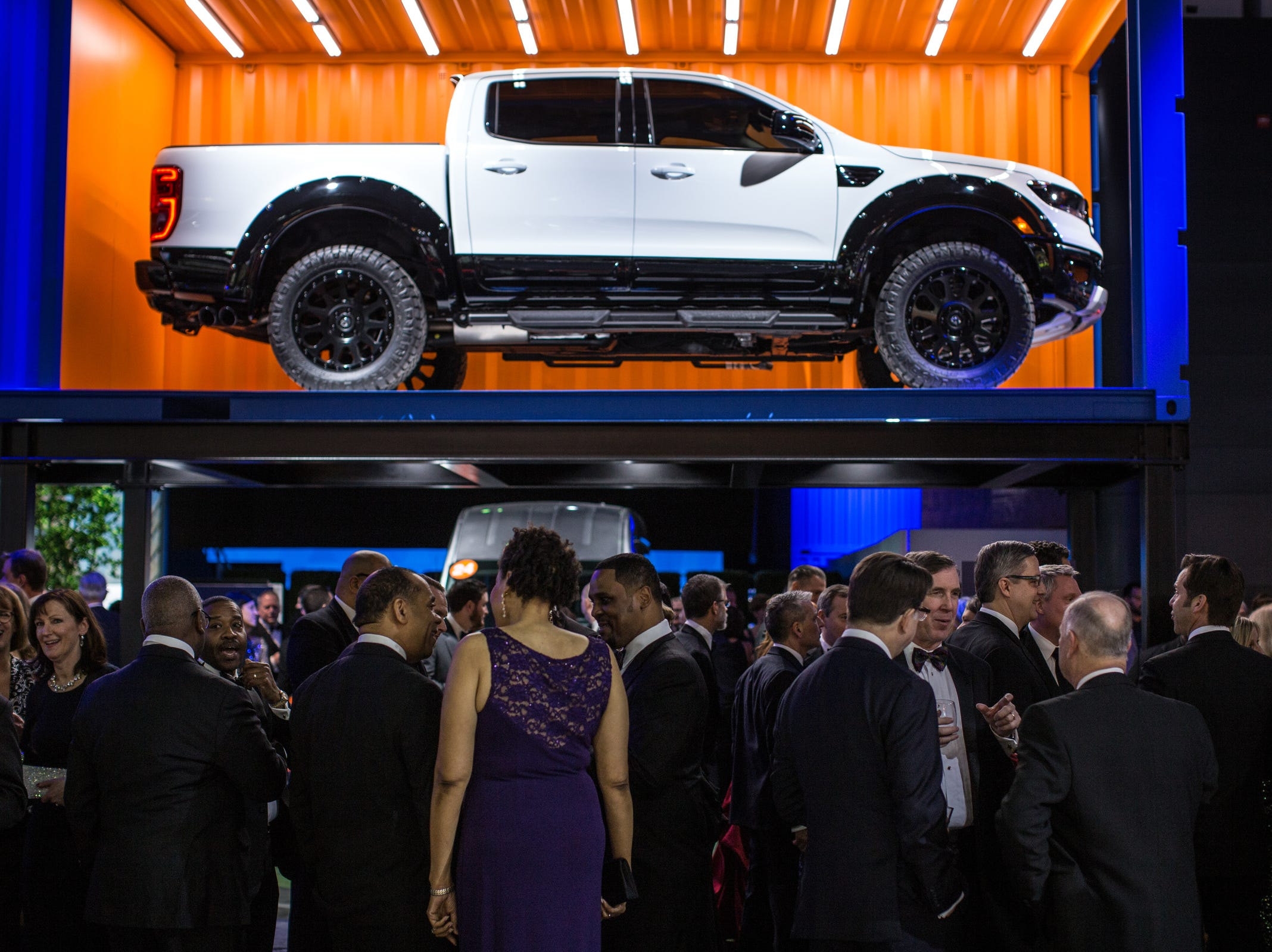 People stand and talk at the Ford display during the 2019 North American International Auto Show Charity Preview at Cobo Center in Detroit on Friday, January 18, 2019.