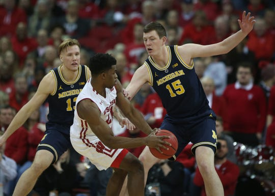 Wisconsin Badgers guard Khalil Iverson dribbles against Michigan Wolverines forward Ignas Brazdeikis, left, and center Jon Teske at the Kohl Center, Jan. 19, 2019.