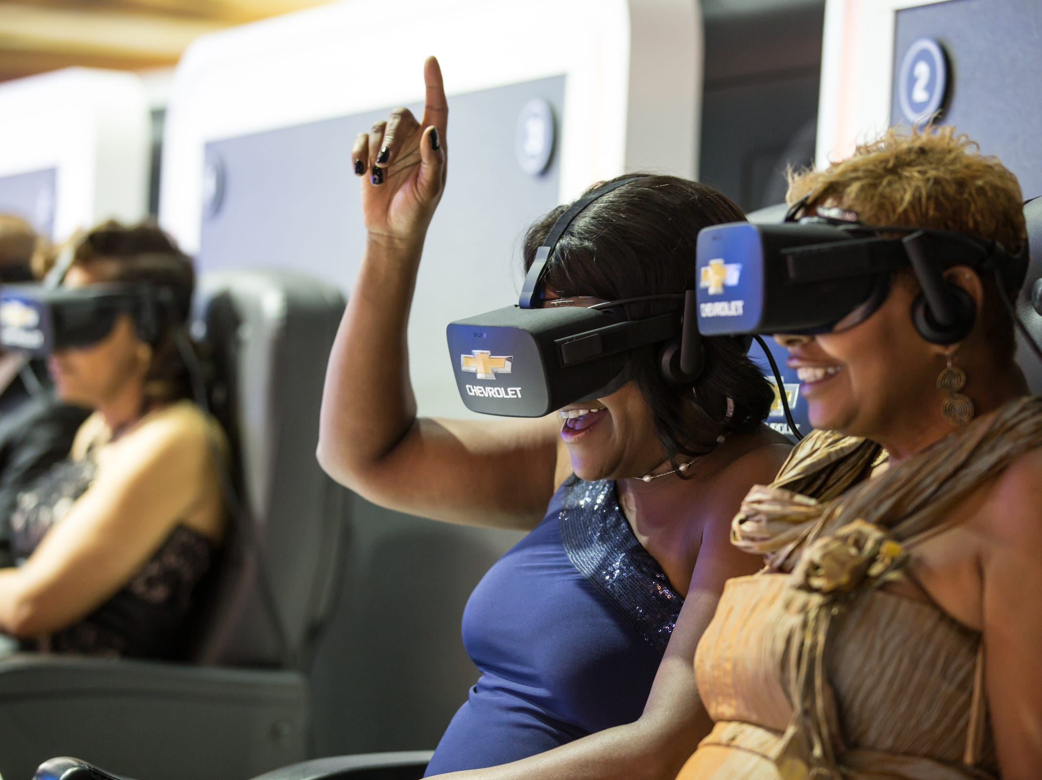 Kim Lindsey-Feagin (right) of Detroit and Donna Mills of Detroit, take a ride on a Virtual Dynamics Lab 4D Experience in the Chevrolet area during the 2019 North American International Auto Show Charity Preview at Cobo Center in Detroit on Friday, January 18, 2019.