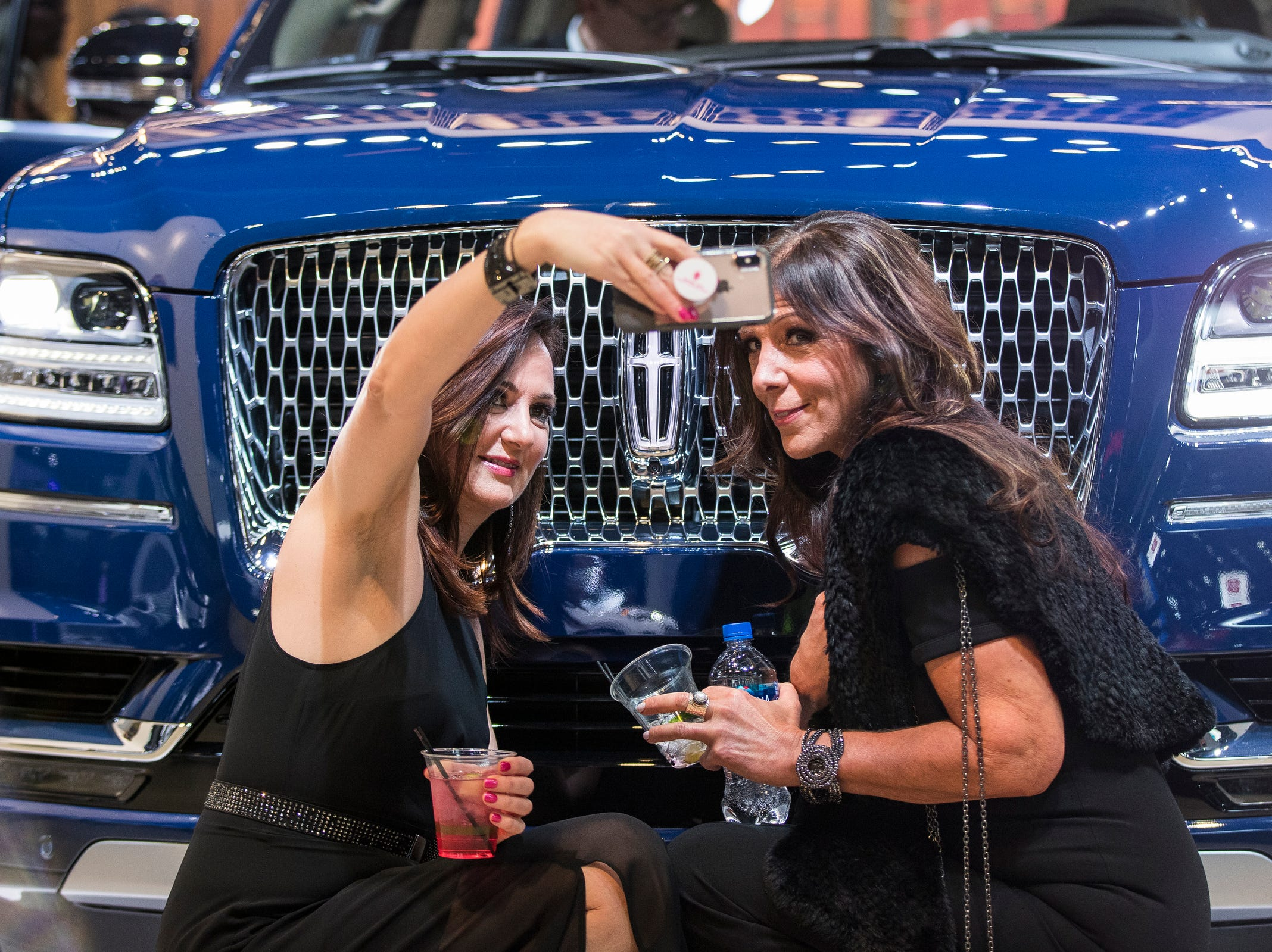 Lisa Jacquin of Novi takes a selfie with her cousin Judy Manoogian of Bloomfield Hills in front of a Lincoln Navigator during the 2019 North American International Auto Show Charity Preview at Cobo Center in Detroit on Friday, January 18, 2019.