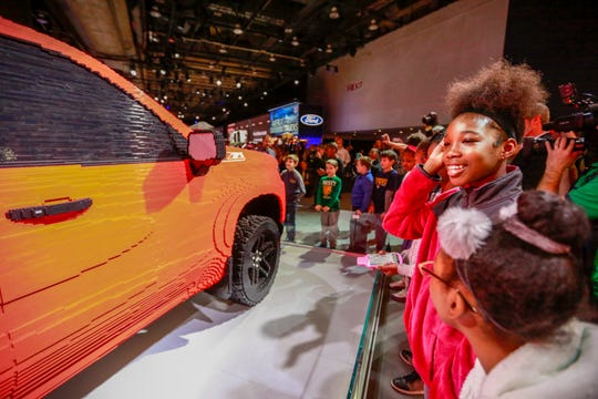 Mariah Burnett, 11, of Detroit joins her classmates from Ralph Waldo Emerson Elementary-Middle School for the Chevrolet unveiling of a 2019 Chevrolet Silverado 1500 Trail Boss made entirely out of LEGOs, during the first public day of the North American International Auto Show at Cobo Center in downtown Detroit on Saturday, Jan. 19, 2019.
