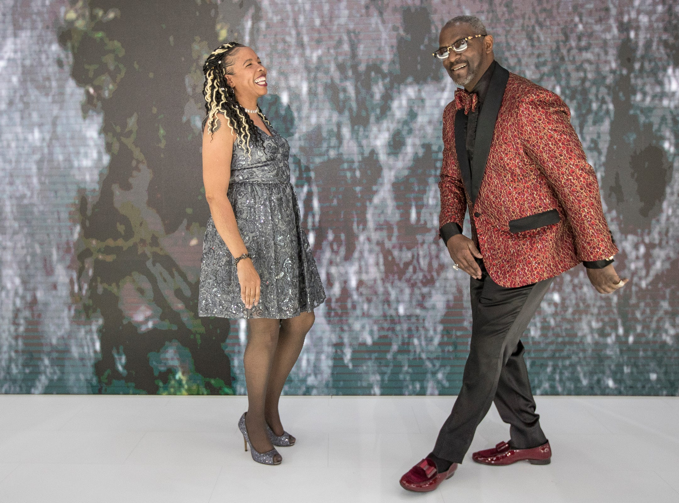 Kathy Parker laughs as her finance Darrell Wilson try to make a dance move at the Kia booth during the 2019 North American International Auto Show Charity Preview at Cobo Center in Detroit on Friday, January 18, 2019.