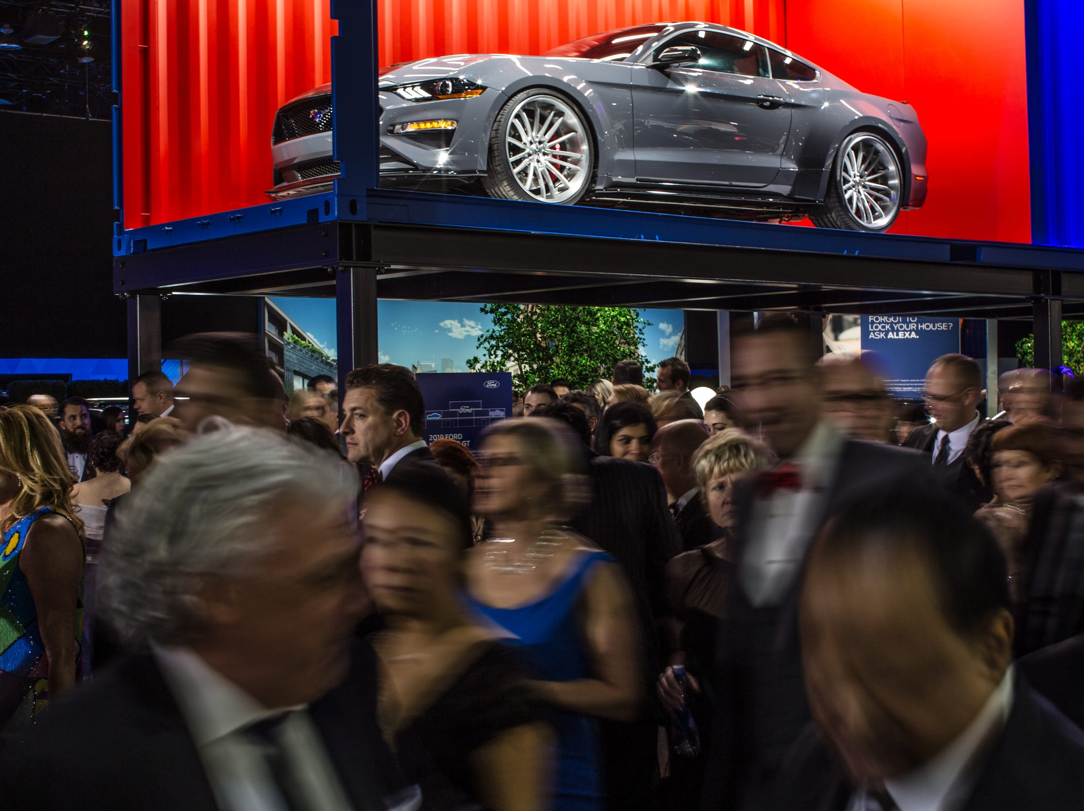 People stroll past the Ford exhibit during the 2019 North American International Auto Show Charity Preview at Cobo Center in Detroit on Friday, January 18, 2019.