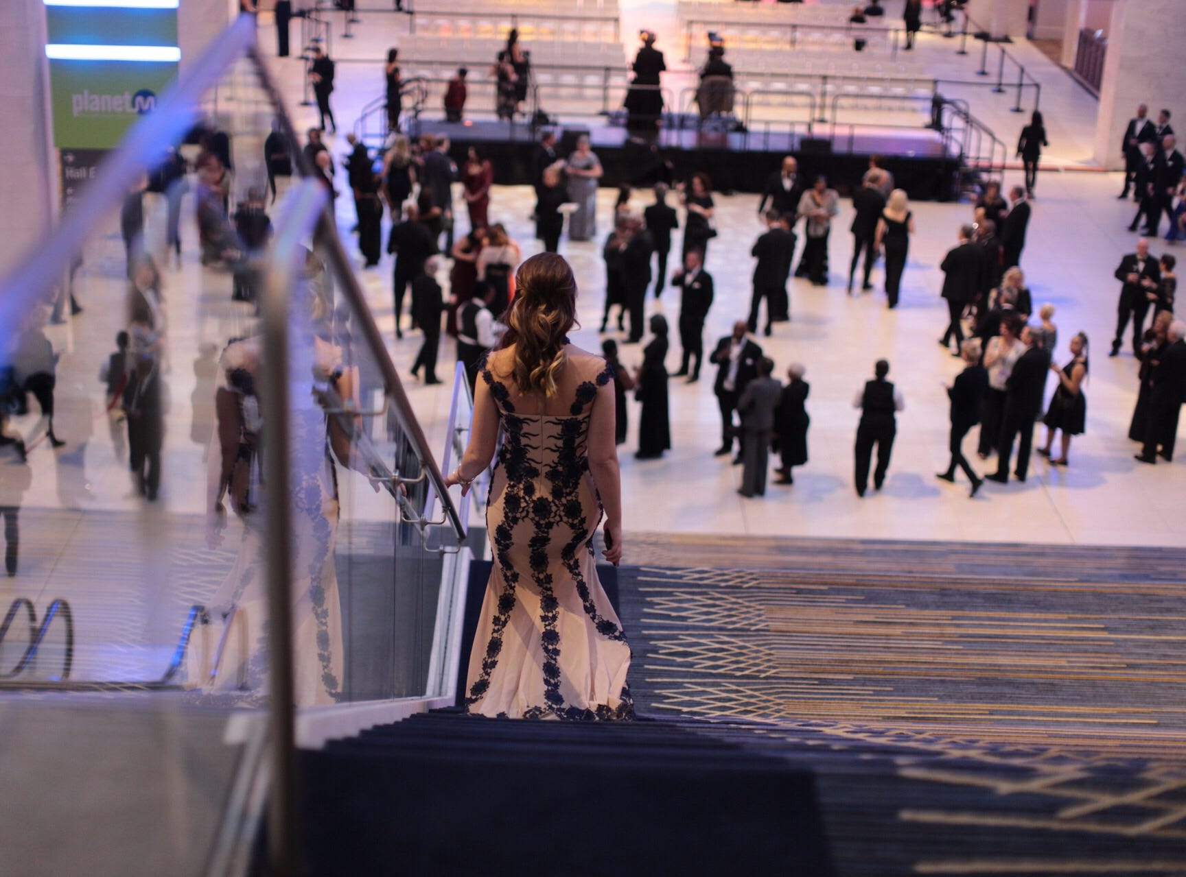 A woman walks Dow for the start of the 2019 North American International Auto Show Charity Preview at Cobo Center in Detroit on Friday, January 18, 2019.