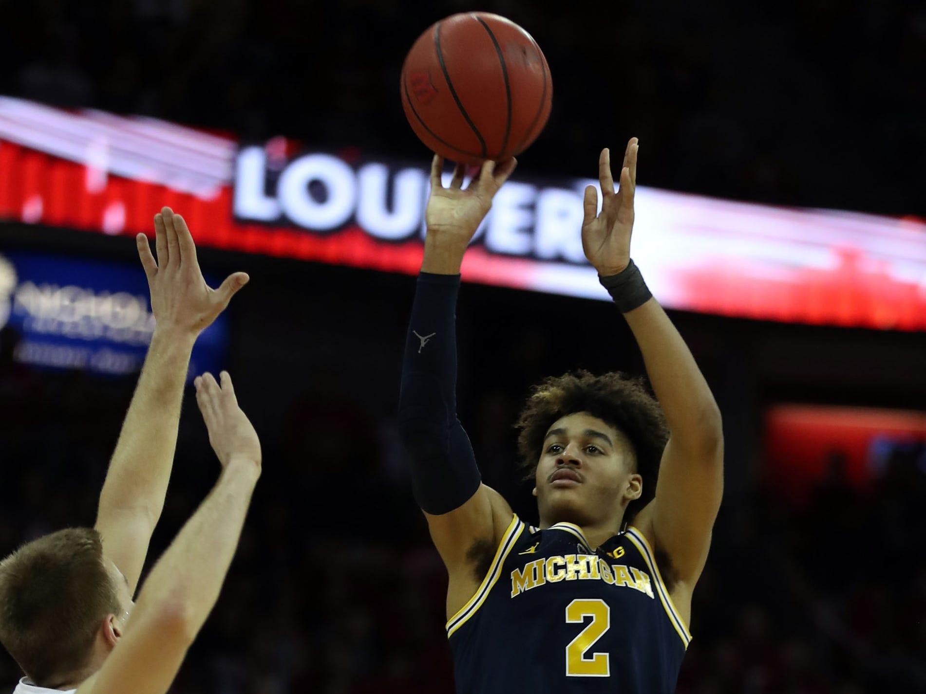 Michigan guard Jordan Poole shoots over Wisconsin guard Brad Davison at the Kohl Center, Jan. 19, 2019 in Madison, Wisc.