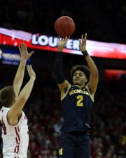 Michigan guard Jordan Poole shoots over Wisconsin guard Brad Davison at the Kohl Center, Jan. 19, 2019 in Madison, Wisc.