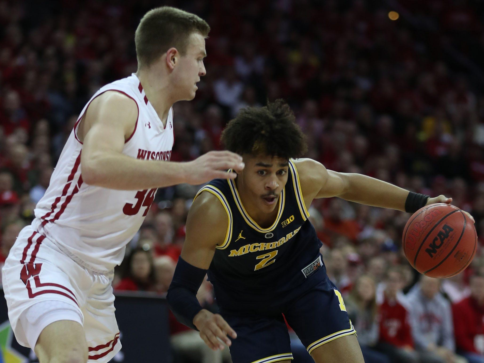 Michigan guard Jordan Poole drives against Wisconsin guard Brad Davison, Jan. 19, 2019 in Madison, Wisc.