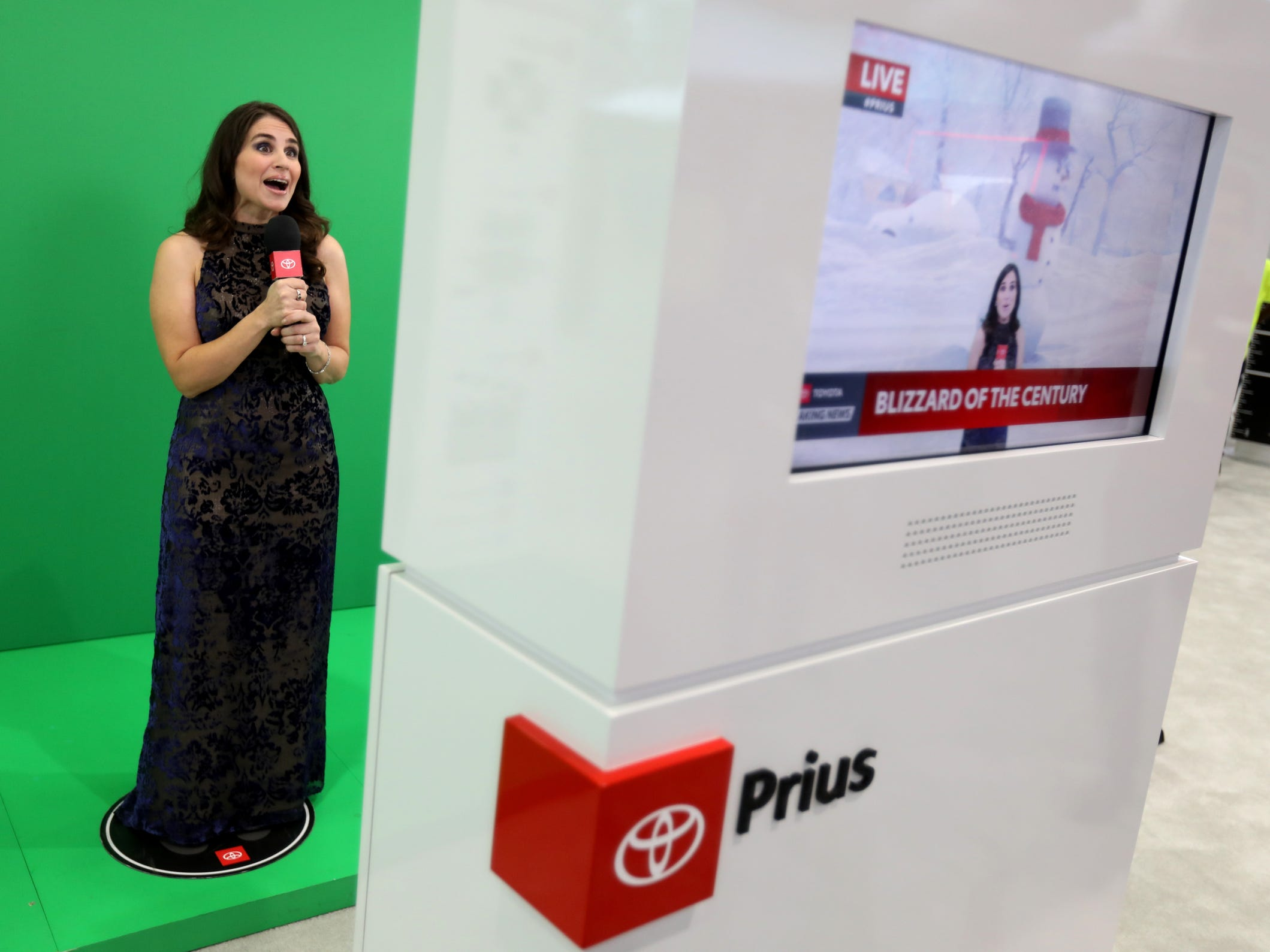 Jennifer Bryant, 47 of Farmington Hills gets into being a meteorologist as she reports the weather at the Toyota Prius location during the 2019 North American International Auto Show Charity Preview at Cobo Center in Detroit on Friday, January 18, 2019.