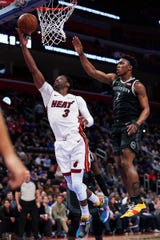 Heat guard Dwyane Wade goes to the basket on Pistons forward Stanley Johnson in the first half at Little Caesars Arena, Friday.