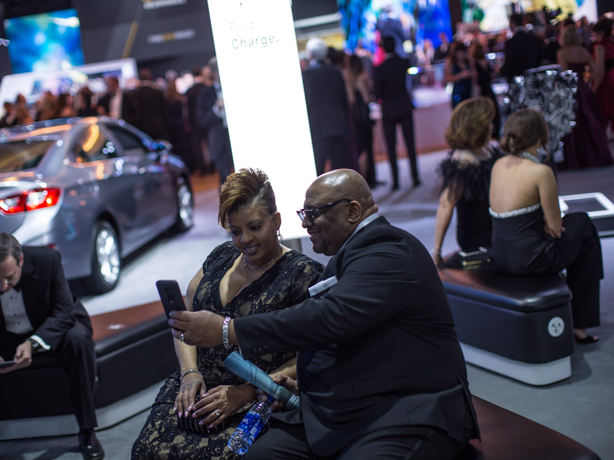 People take a photo while sitting in the Chevrolet area during the 2019 North American International Auto Show Charity Preview at Cobo Center in Detroit on Friday, January 18, 2019.