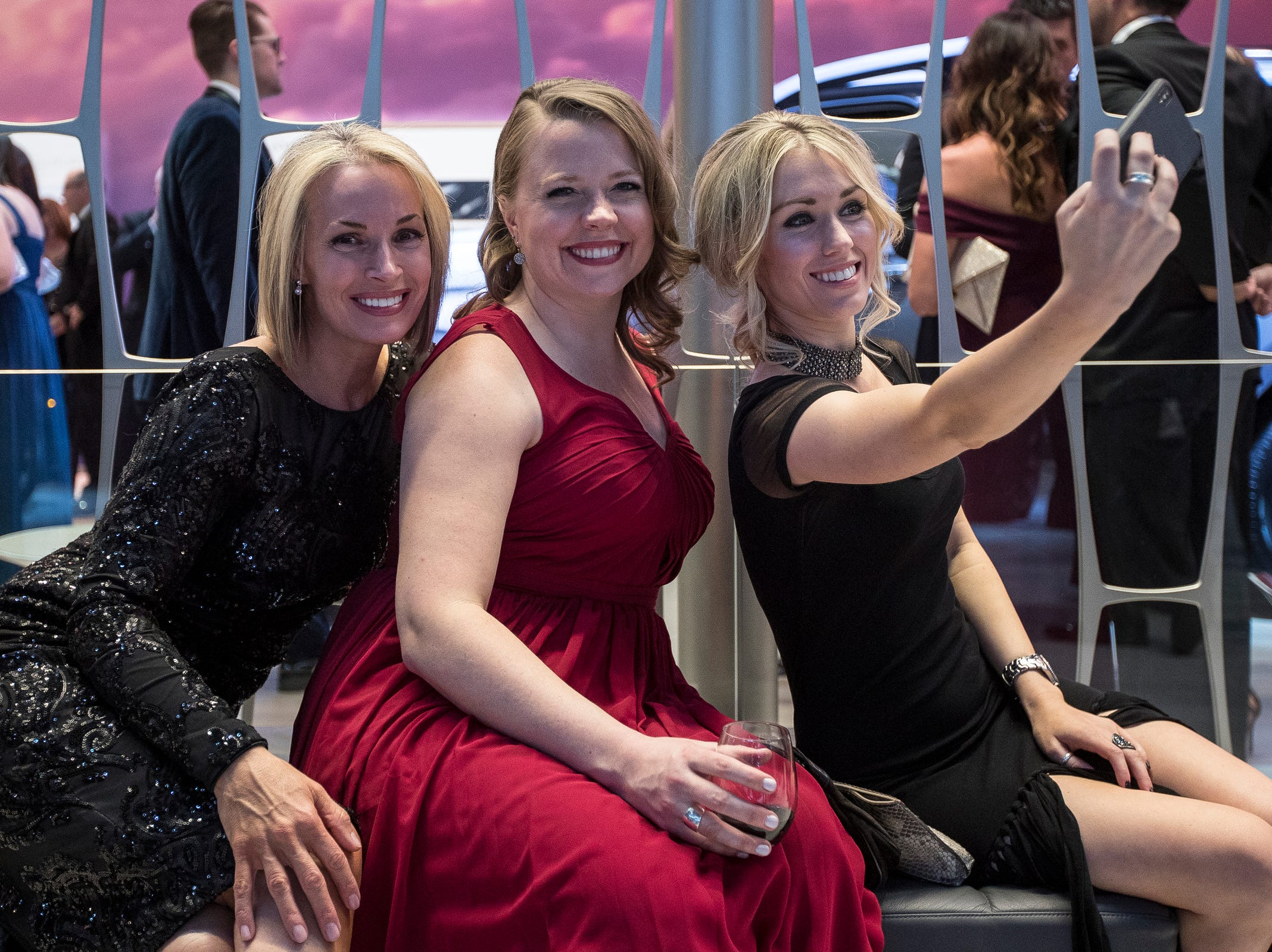 From left, Jena Campbell, Emily Falconer and Heather Oldani pose for a photo in the Lincoln booth during the 2019 North American International Auto Show Charity Preview at Cobo Center in Detroit on Friday, January 18, 2019.