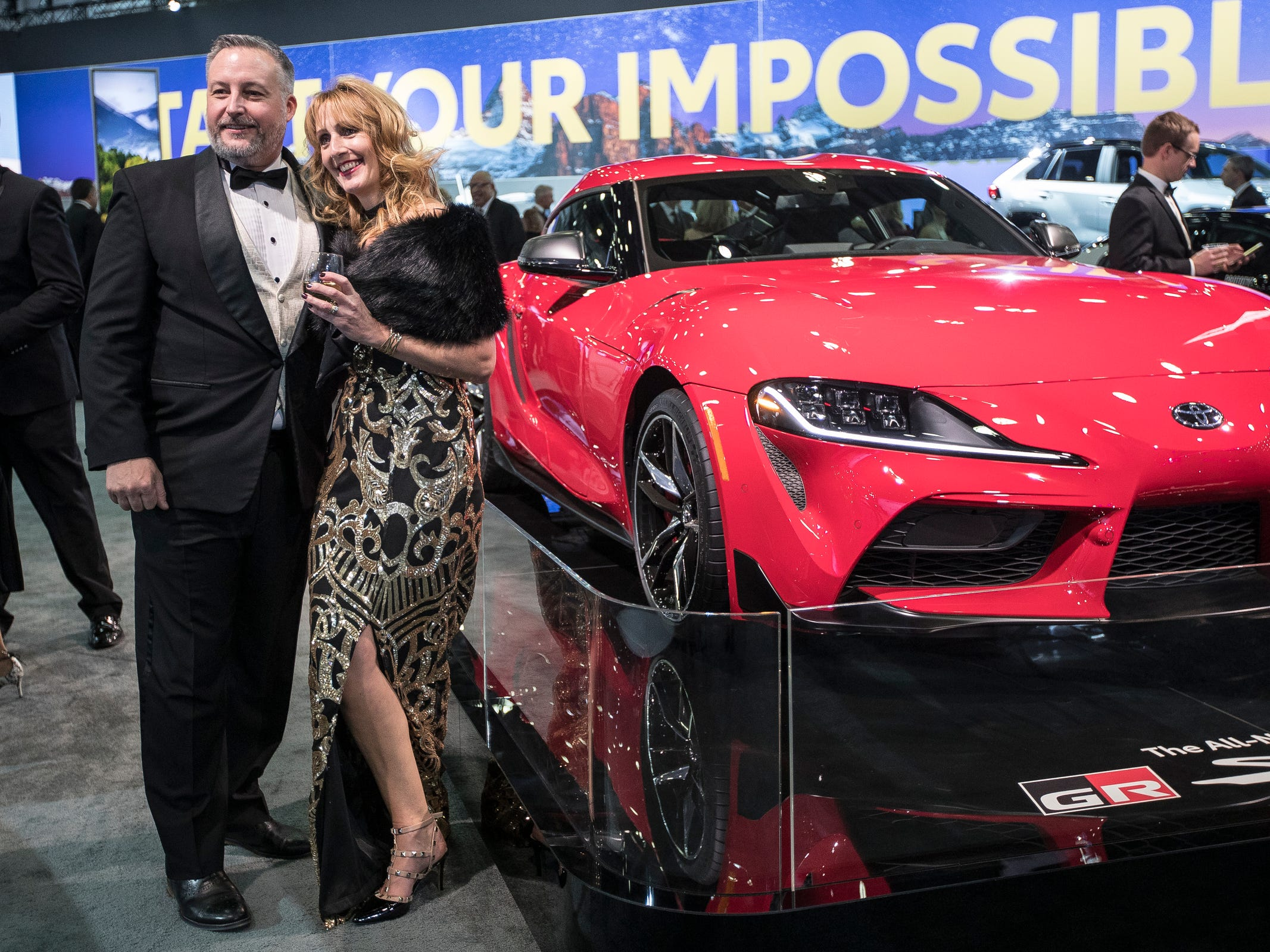 Paul and Jane Heasman of Rochester Hills pose for a phot next to 2019 Toyota Supra during the 2019 North American International Auto Show Charity Preview at Cobo Center in Detroit on Friday, January 18, 2019.