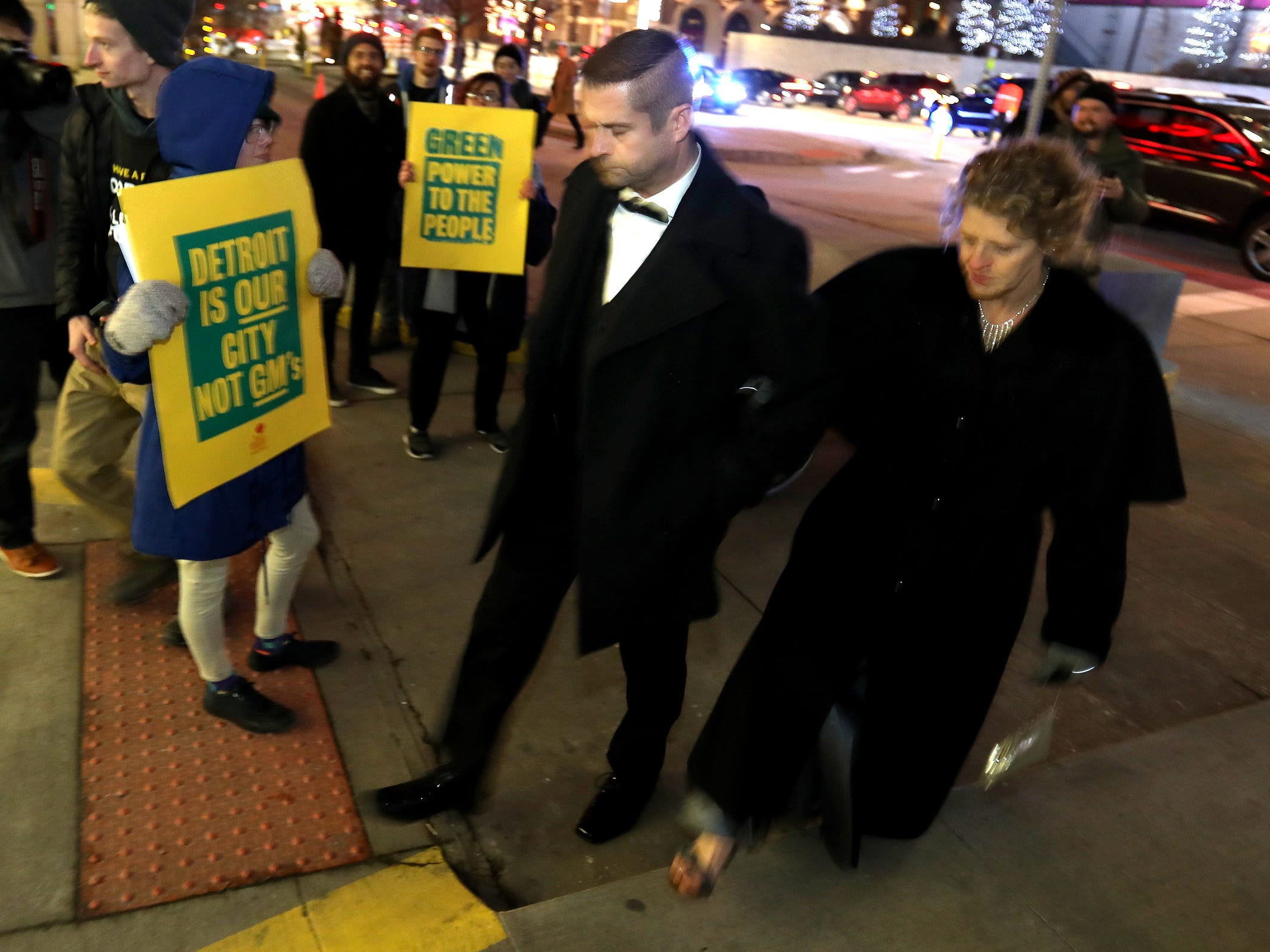 Attendees of the 2019 North American International Auto Show Charity Preview at Cobo Center quickly walk pass protestors and try to get into the event on Friday, January 18, 2019.