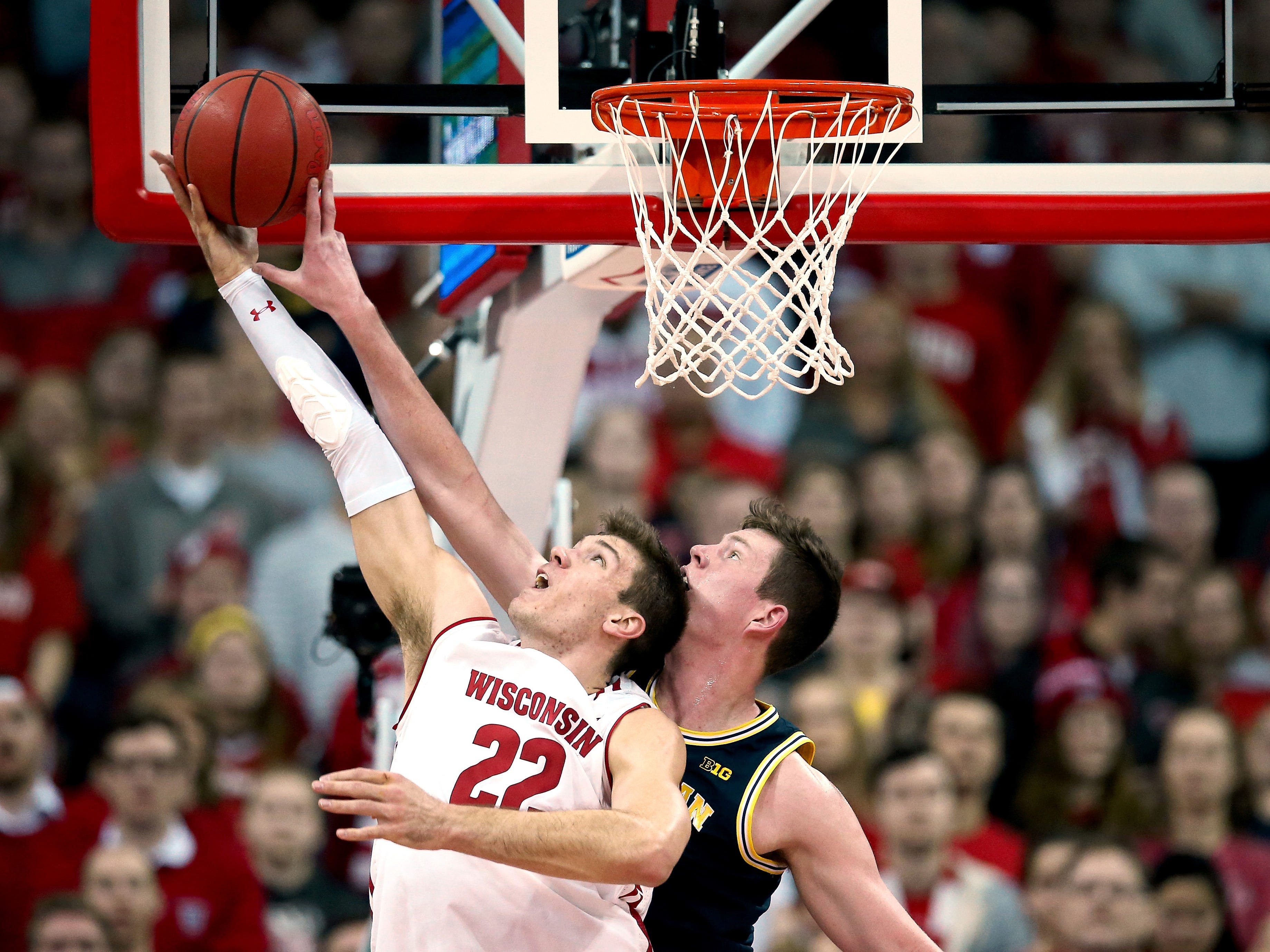 Michigan's Jon Teske blocks a shot attempt by Wisconsin's Ethan Happ in the first half at the Kohl Center on Jan. 19, 2019 in Madison, Wisc.