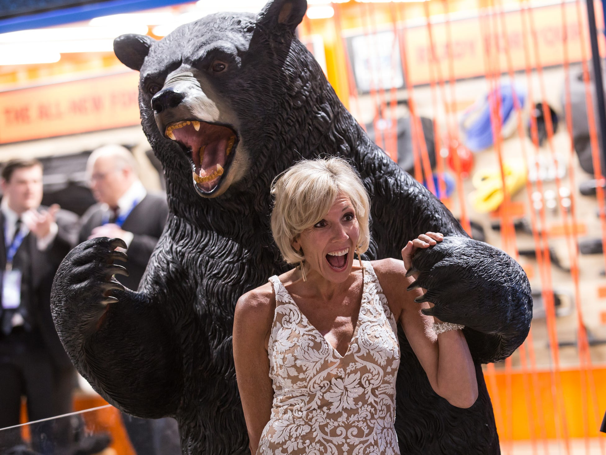 A woman poses with a bear statue in the Ford section during the 2019 North American International Auto Show Charity Preview at Cobo Center in Detroit on Friday, January 18, 2019.