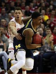 Wisconsin guard Kobe King fouls Michigan guard Charles Matthews at the Kohl Center, Jan. 19, 2019 in Madison, Wisc.