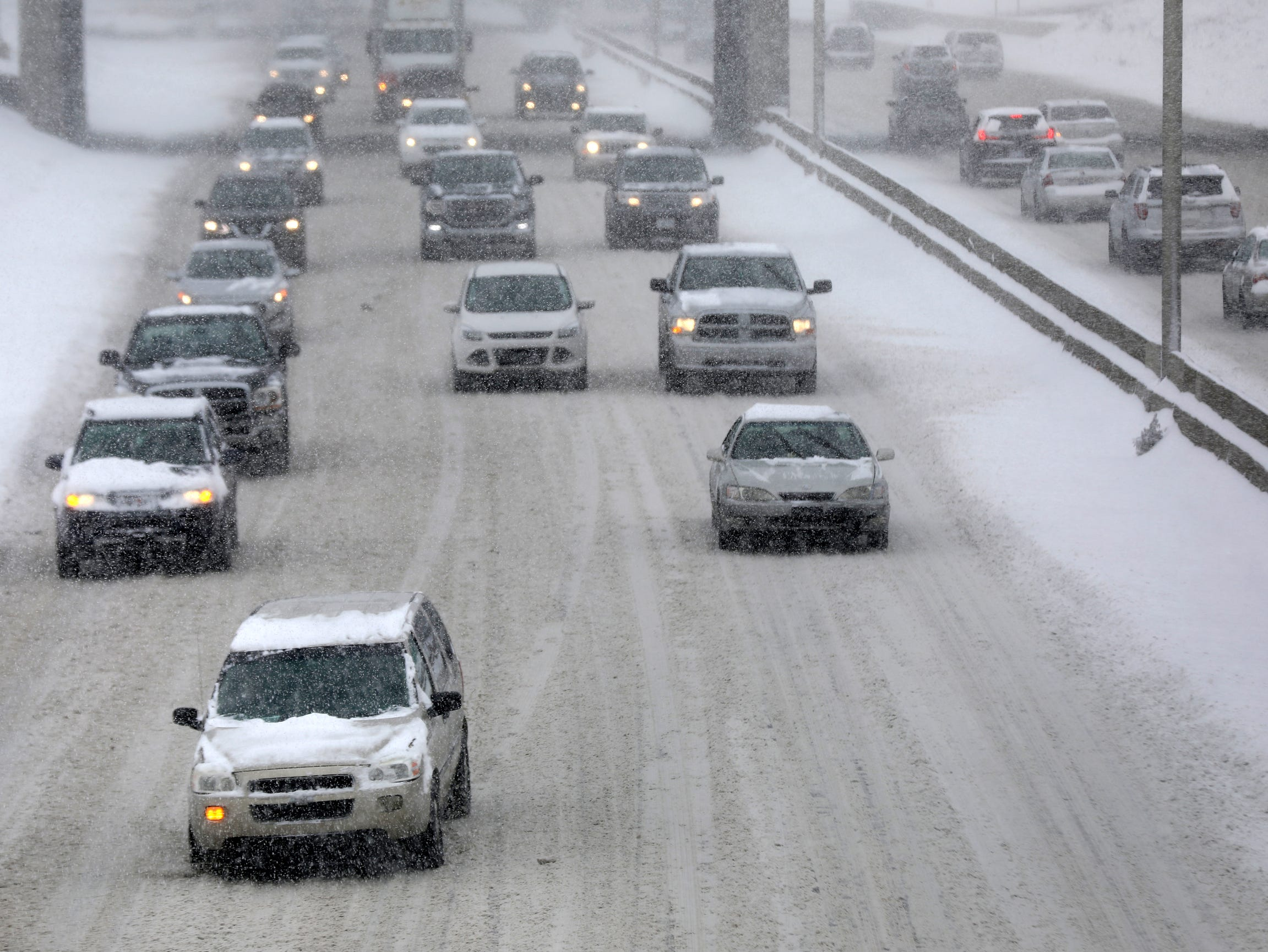 Vehicles travel East on I-94 in Detroit on the snow covered and slippery freeway.