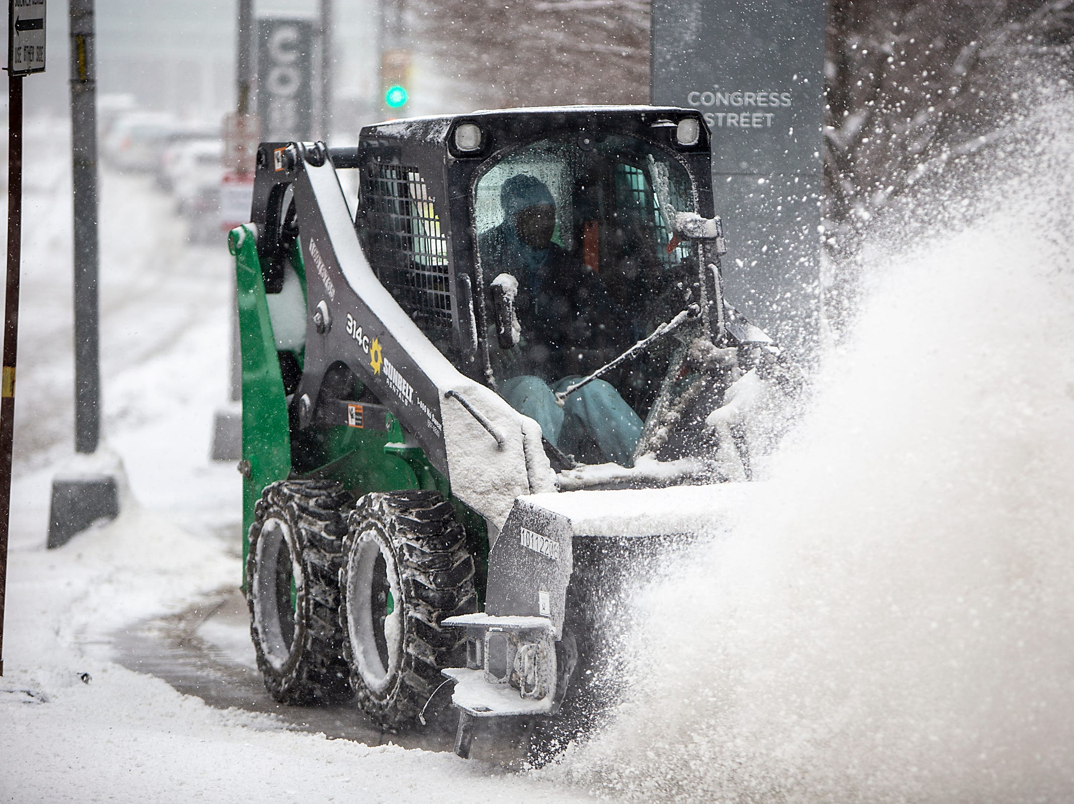 The snow is plowed from the sidewalks during the start of the North American International Auto Show at Cobo Center in downtown Detroit on Saturday, Jan. 19, 2019.