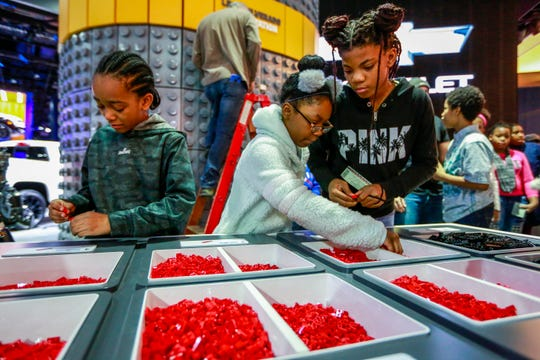 Michael Dowe, 10; from the left, Sarah Evans, 10 and Akyah Burell, 12, all prototypes of Detroit builda at the LEGO Silverado construction station, during the start of the North American International Auto Show at Cobo Center in downtown Detroit on Saturday, January 19 of 2019.