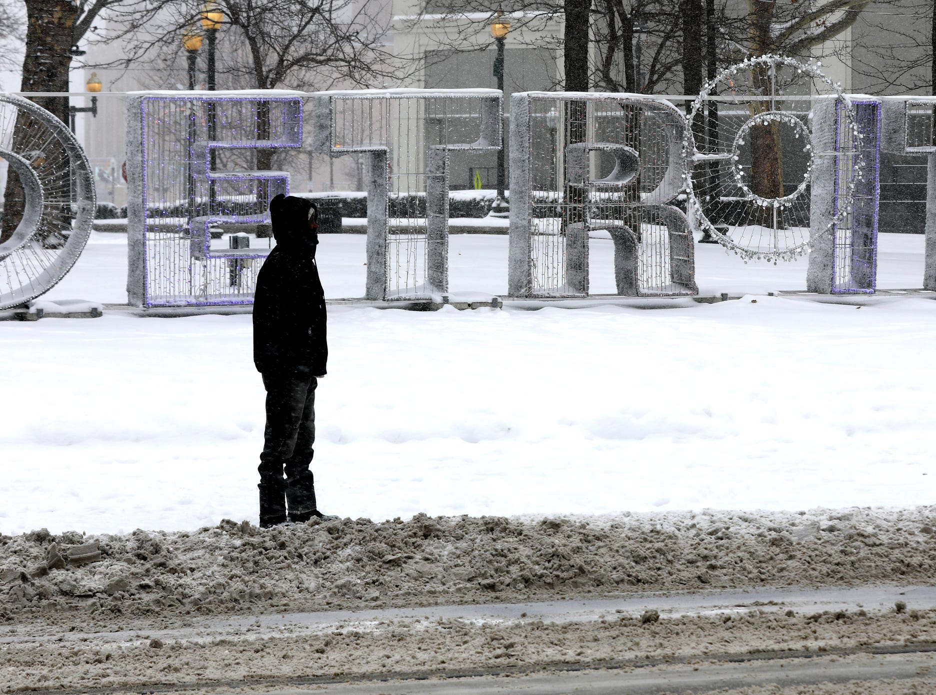 Waiting near a Detroit art installation sign at Grand Circus Park, Calvin, Brown, 64 of Detroit looks South down Woodward Avenue for any sign of a city bus making its way up the avenue on Saturday, January 19, 2019.