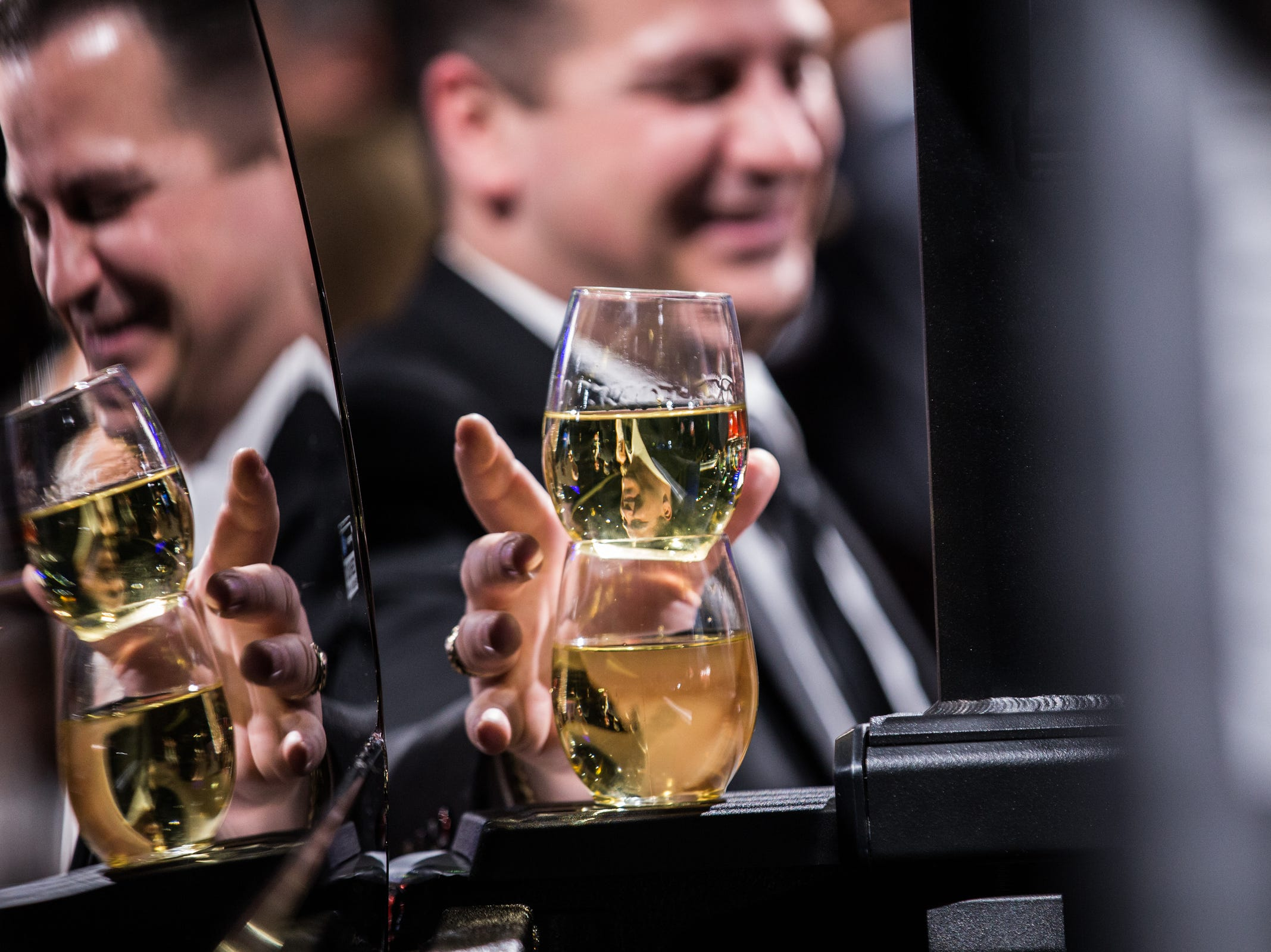 A man grabs his wine glasses stacked on a vehicle in the Ford section during the 2019 North American International Auto Show Charity Preview at Cobo Center in Detroit on Friday, January 18, 2019.
