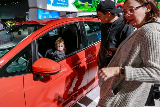 Milo Dresser, 2, of Royal Oak hops into the driver seat of the 2019 Honda Fit 5DR EX, while his parents Britt (30) and Andy (32) Dresser look on during the start of the North American International Auto Show at Cobo Center in downtown Detroit on Saturday, Jan. 19, 2019.
