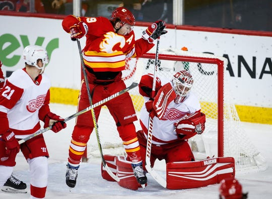 Wings goalie Jimmy Howard has a shot deflect off his helmet as Flames' Matthew Tkachuk jumps in the second period Friday in Calgary, Alberta.