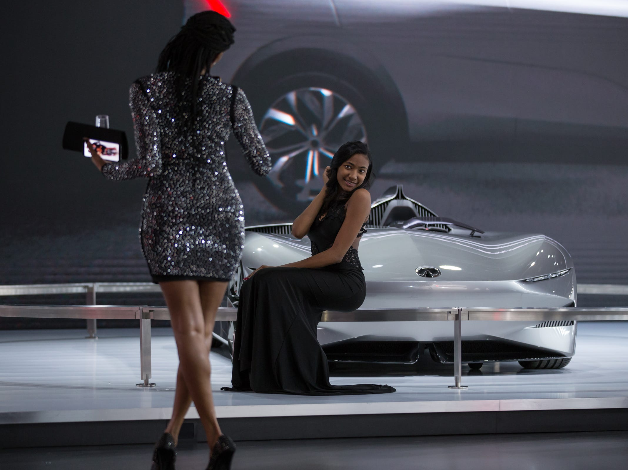 Sharon Freed-Moreland of Detroit takes a photo of her daughter Ellissa Freed next to the Infiniti Prototype 10 during the 2019 North American International Auto Show Charity Preview at Cobo Center in Detroit on Friday, January 18, 2019.