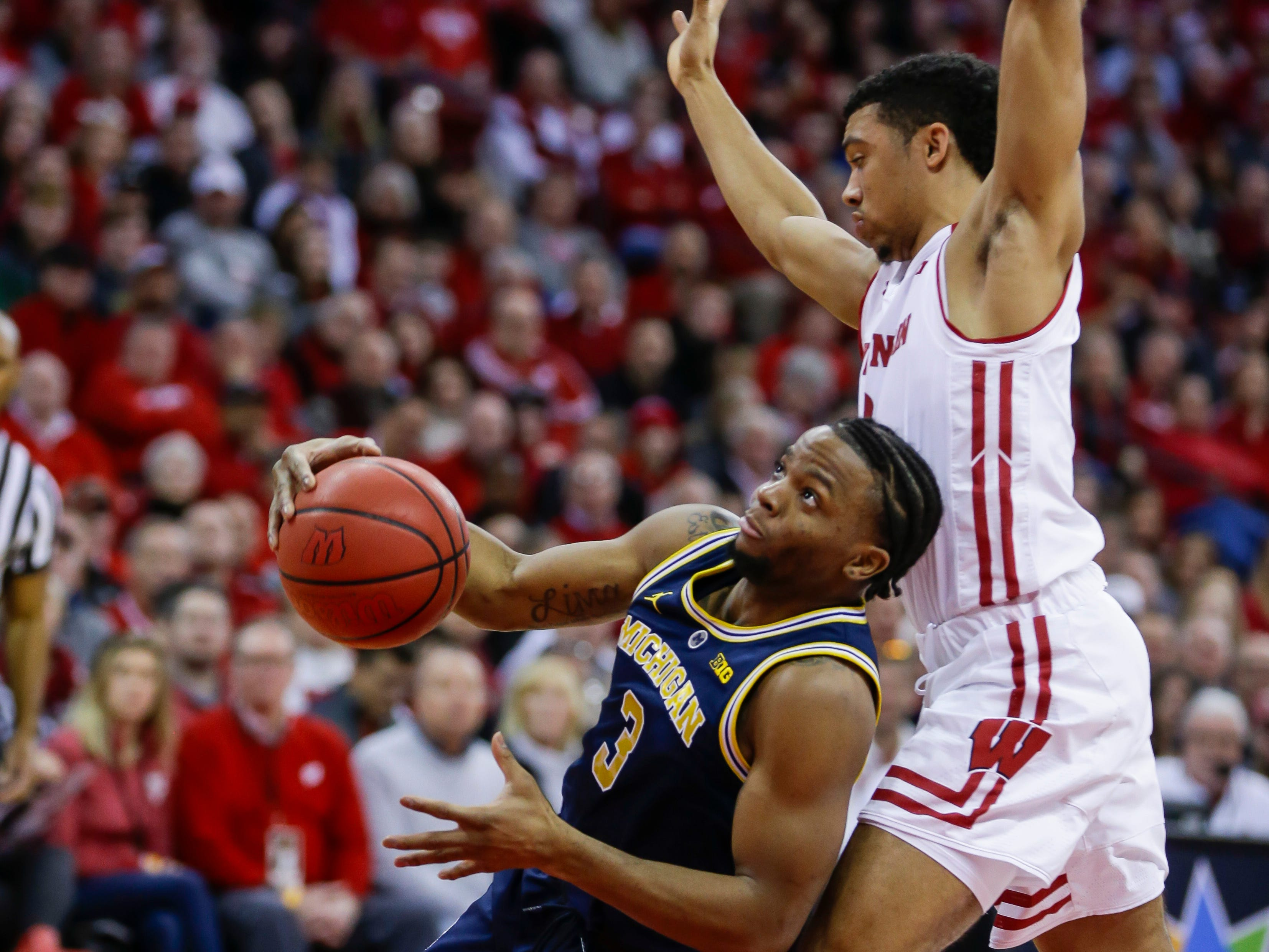 Michigan's Zavier Simpson slips while driving against Wisconsin's D'Mitrik Trice on Saturday, Jan. 19, 2019, in Madison, Wis.