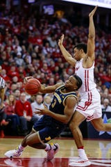 Zavier Simpson slips while driving against Wisconsin's D'Mitrik Trice on  Jan. 19 in Madison, Wis.