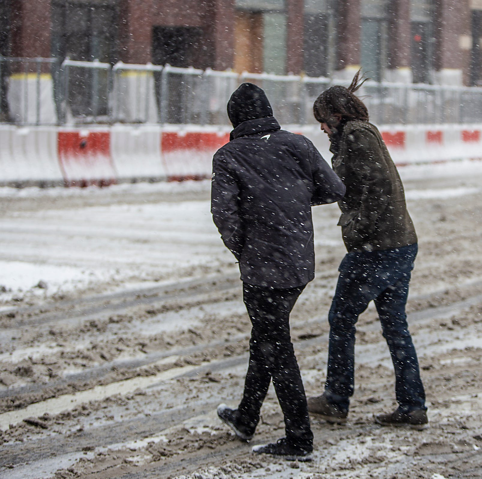 People cross the street in the snow, during the start of the public days at the North American International Auto Show at Cobo Center in downtown Detroit on Saturday, Jan. 19, 2019.