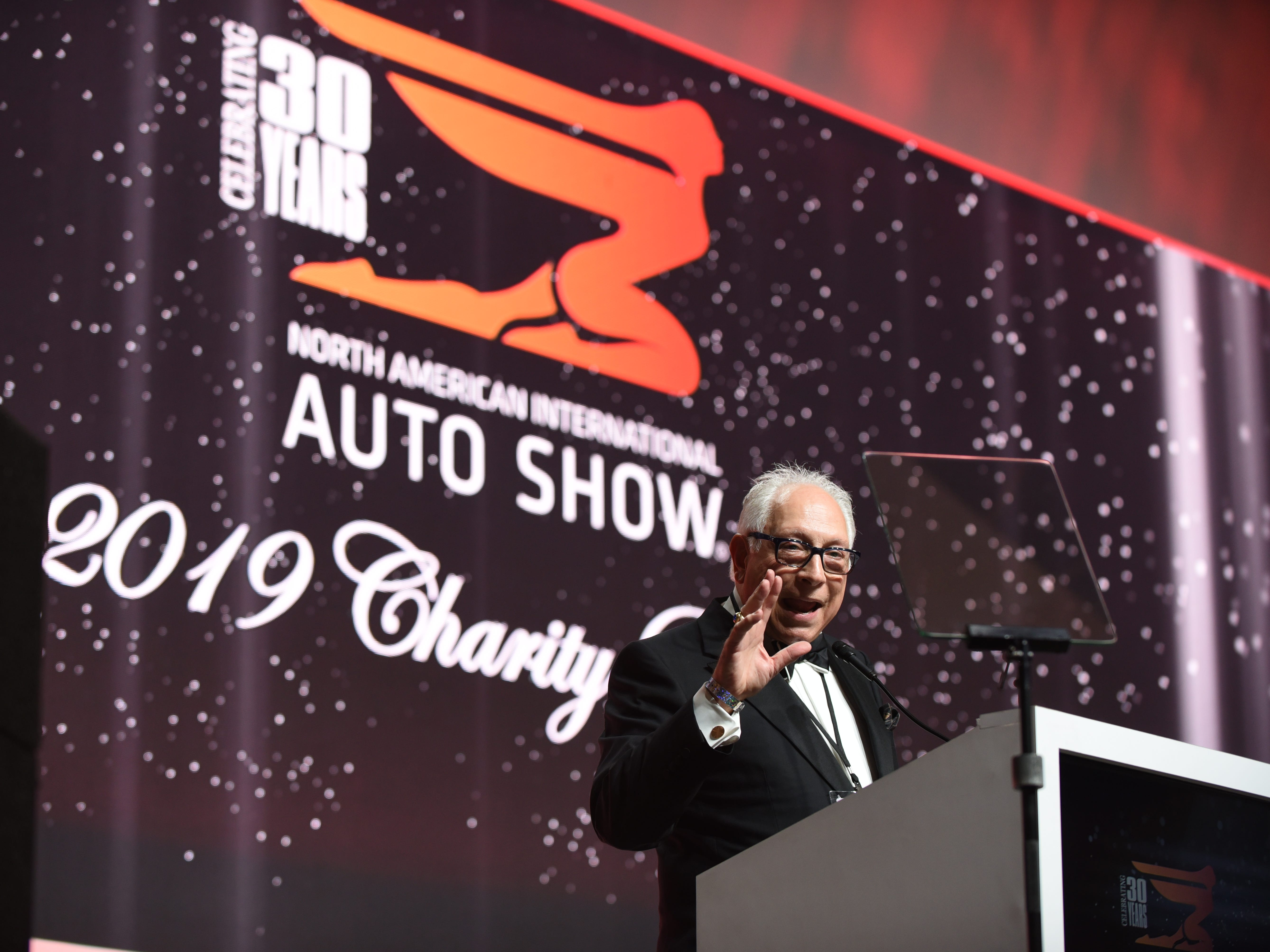 Emcee Paul W. Smith speaks about the final winter auto show on the atrium stage at the 2019 Auto Show Charity Preview ribbon-cutting ceremony.