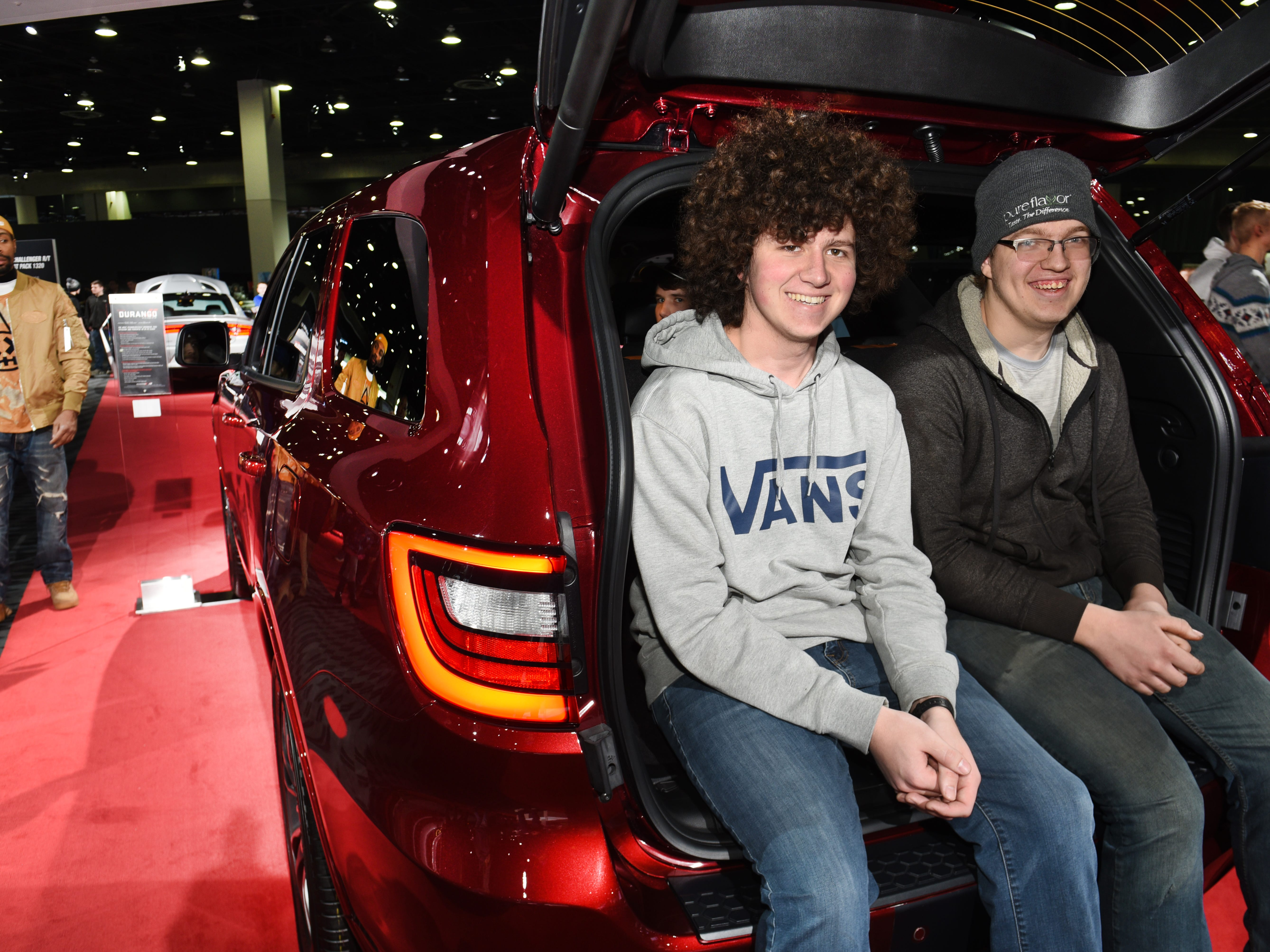 Travis Neafeld (left) and Jimmy Berg sit in the rear cargo area of the 2019 Dodge Durango at the 2019 North American International Auto Show .